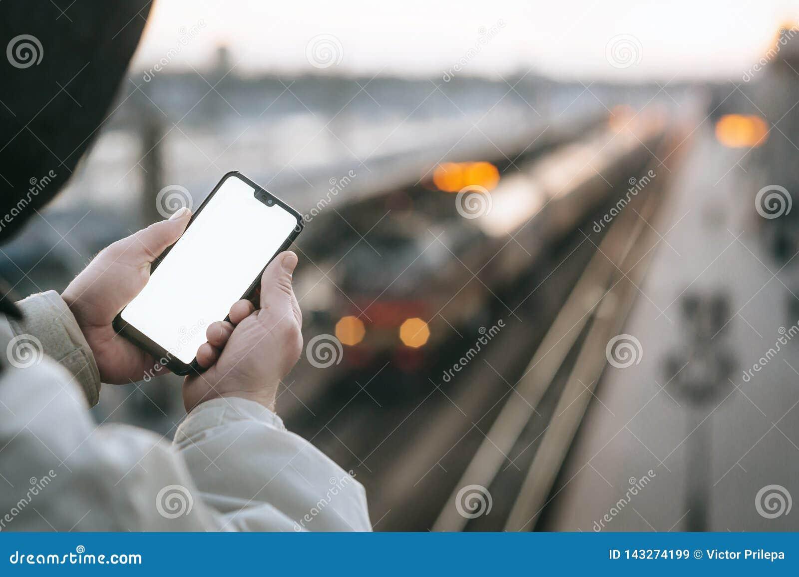 O homem está guardando um smartphone ascendente trocista em sua mão, na perspectiva do trem na estação de trem