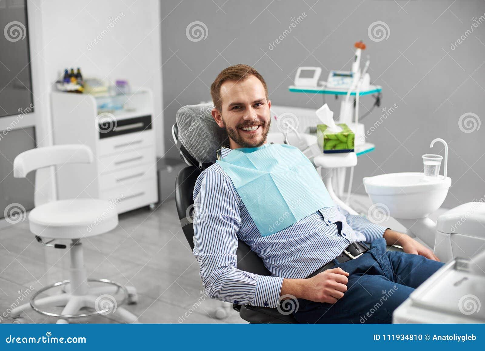 O homem está sorrindo à câmera ao sentar-se em uma cadeira dental na odontologia que é feliz e satisfeita com seu tratamento