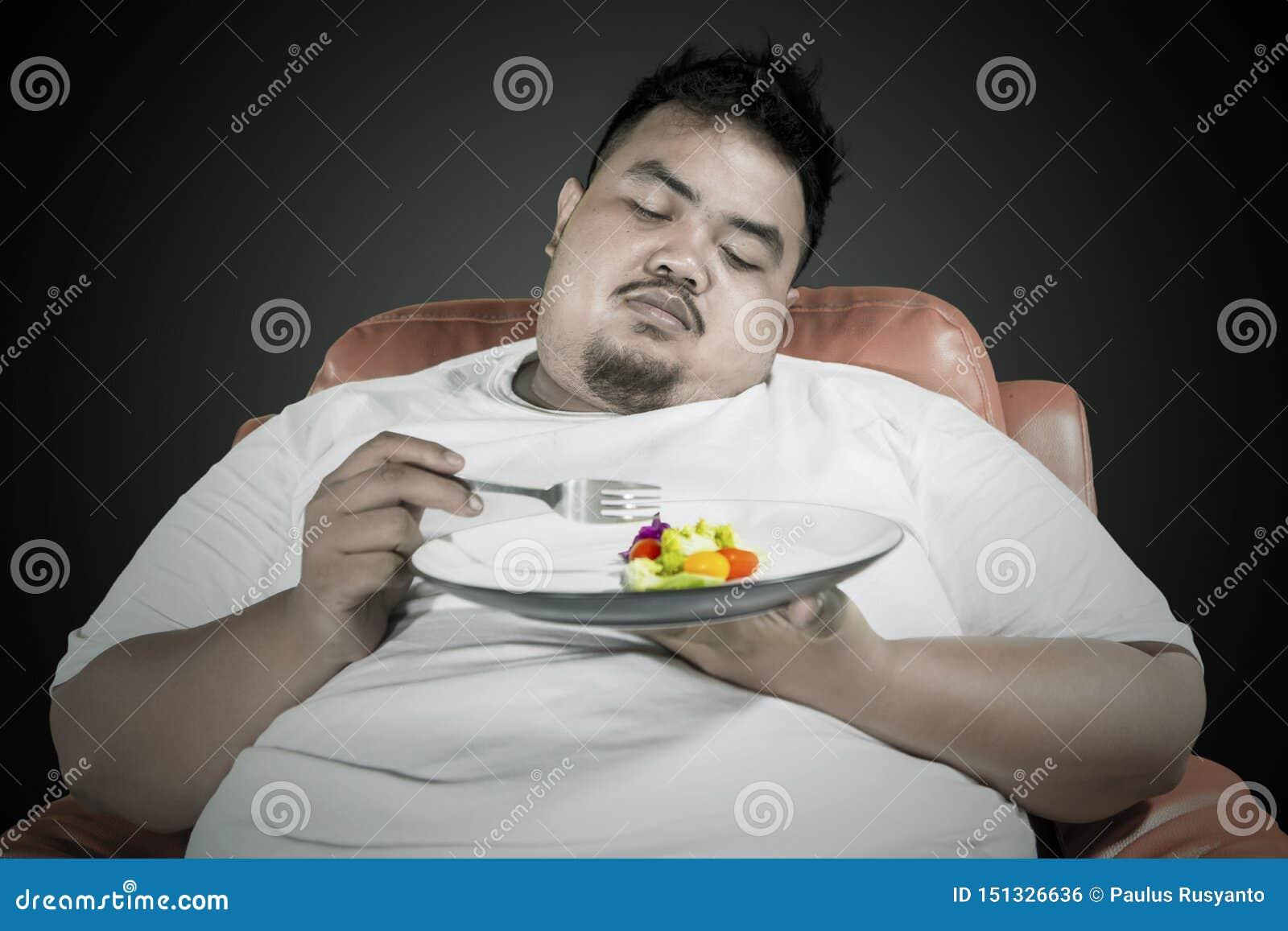 O homem excesso de peso preguiçoso come o alimento saudável