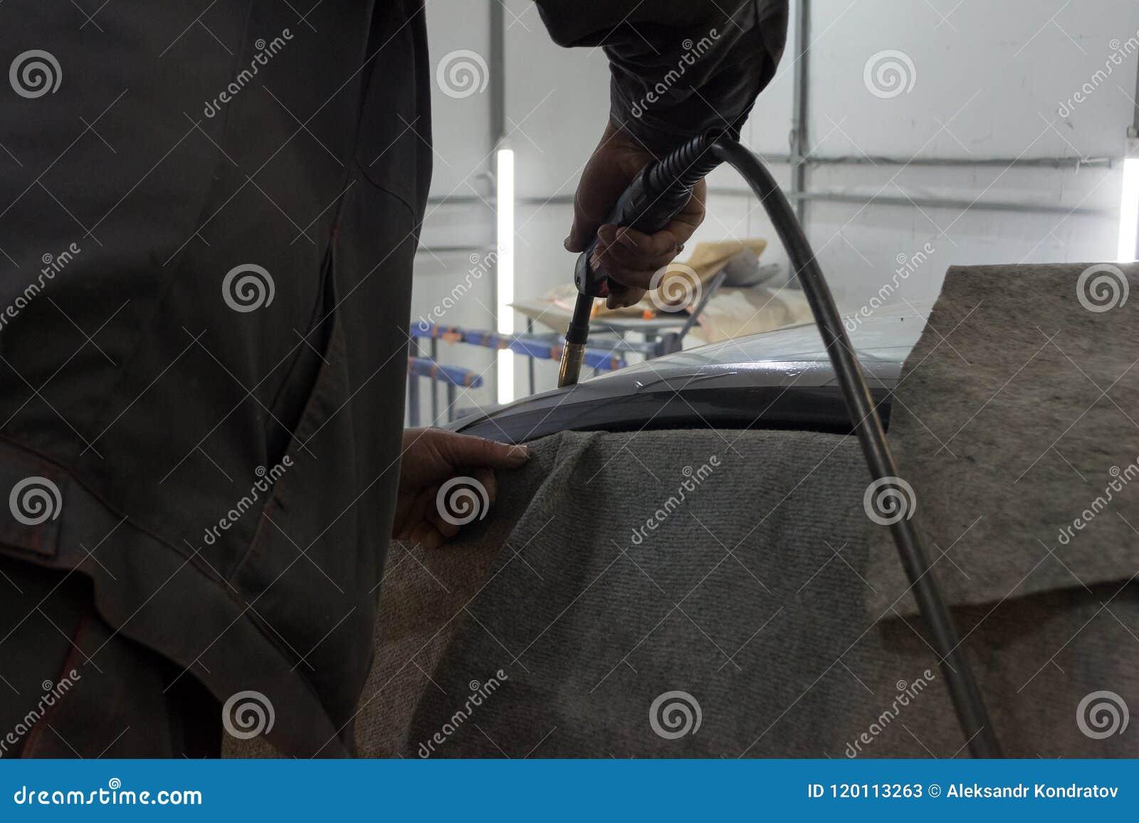O homem experiente executa o trabalho no carro do reparo do corpo com uma máquina de soldadura