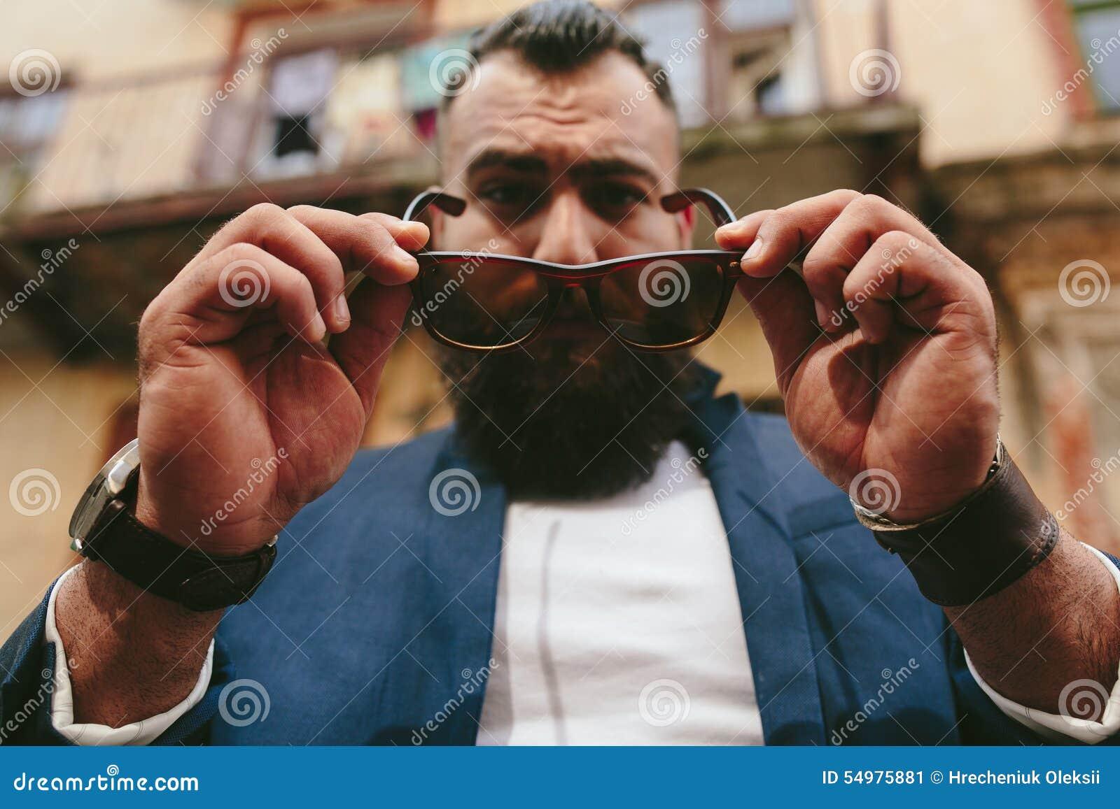 O homem farpado fresco à moda decola seus vidros