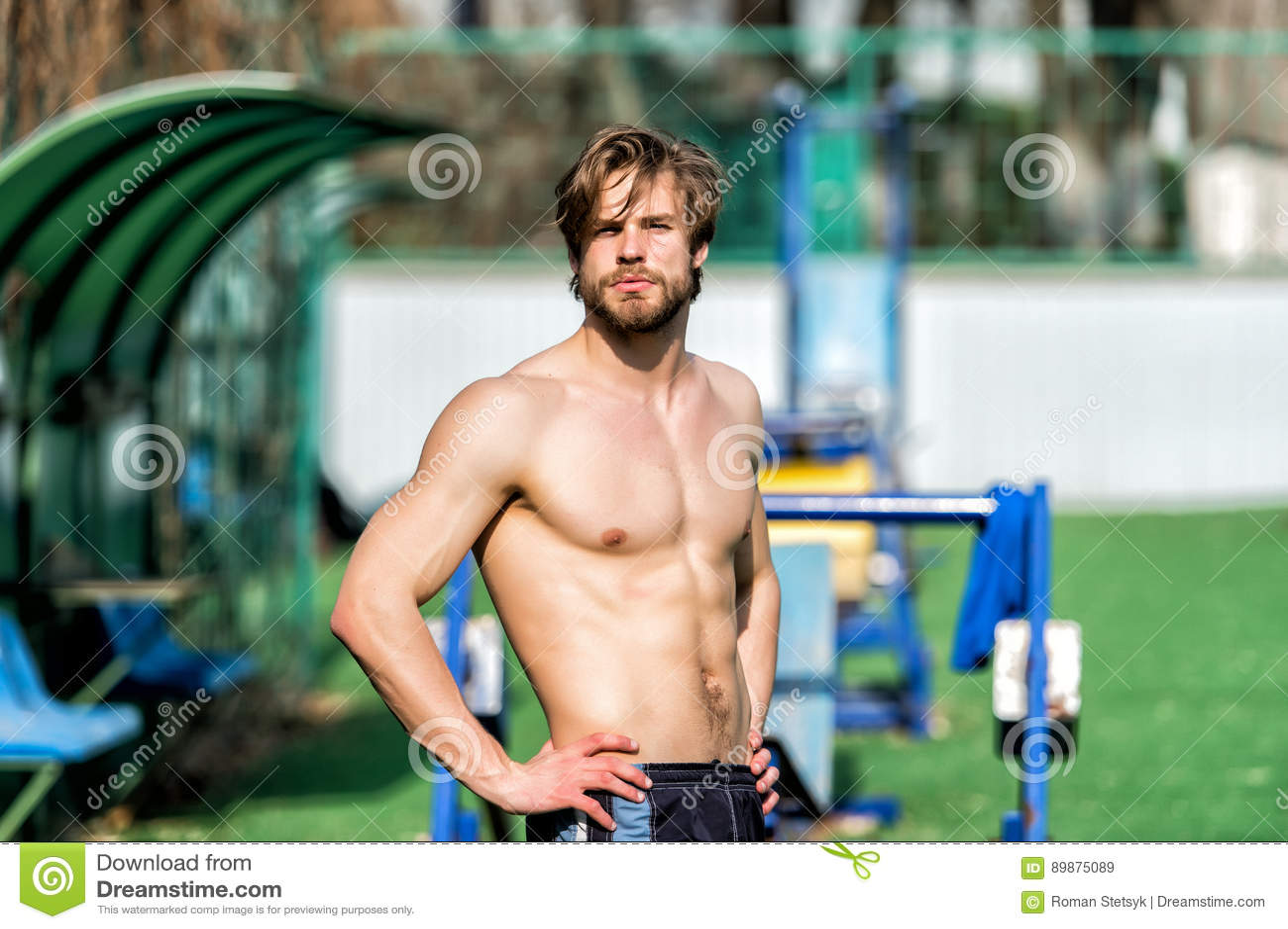 O homem farpado tem o cabelo à moda, corpo atlético relaxa no estádio