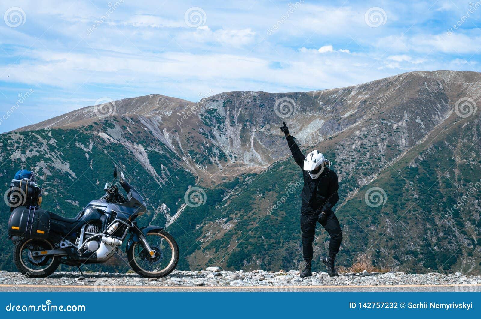O homem feliz do motociclista está dançando e velomotor da aventura na parte superior da montanha Viagem da motocicleta Mundo que