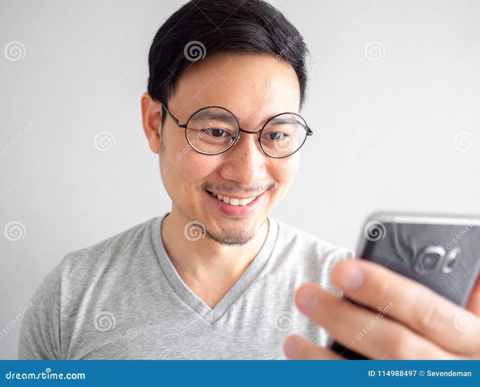 O homem feliz est? usando o smartphone Conceito de usar meios sociais sobre