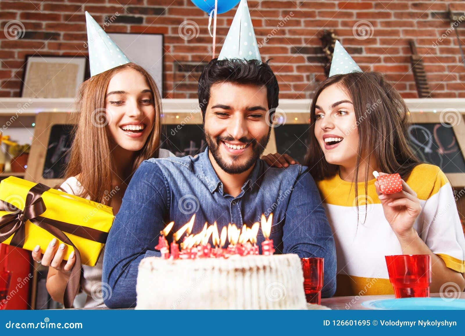 O homem funde para fora velas no bolo branco