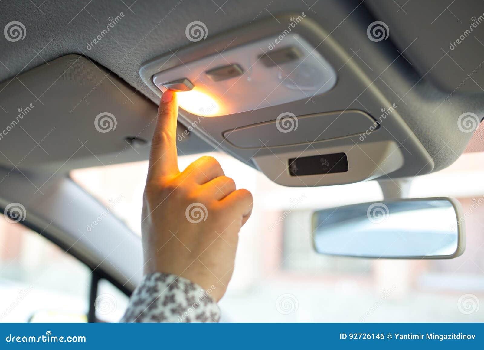 O homem gerencie sobre a luz no teto no carro