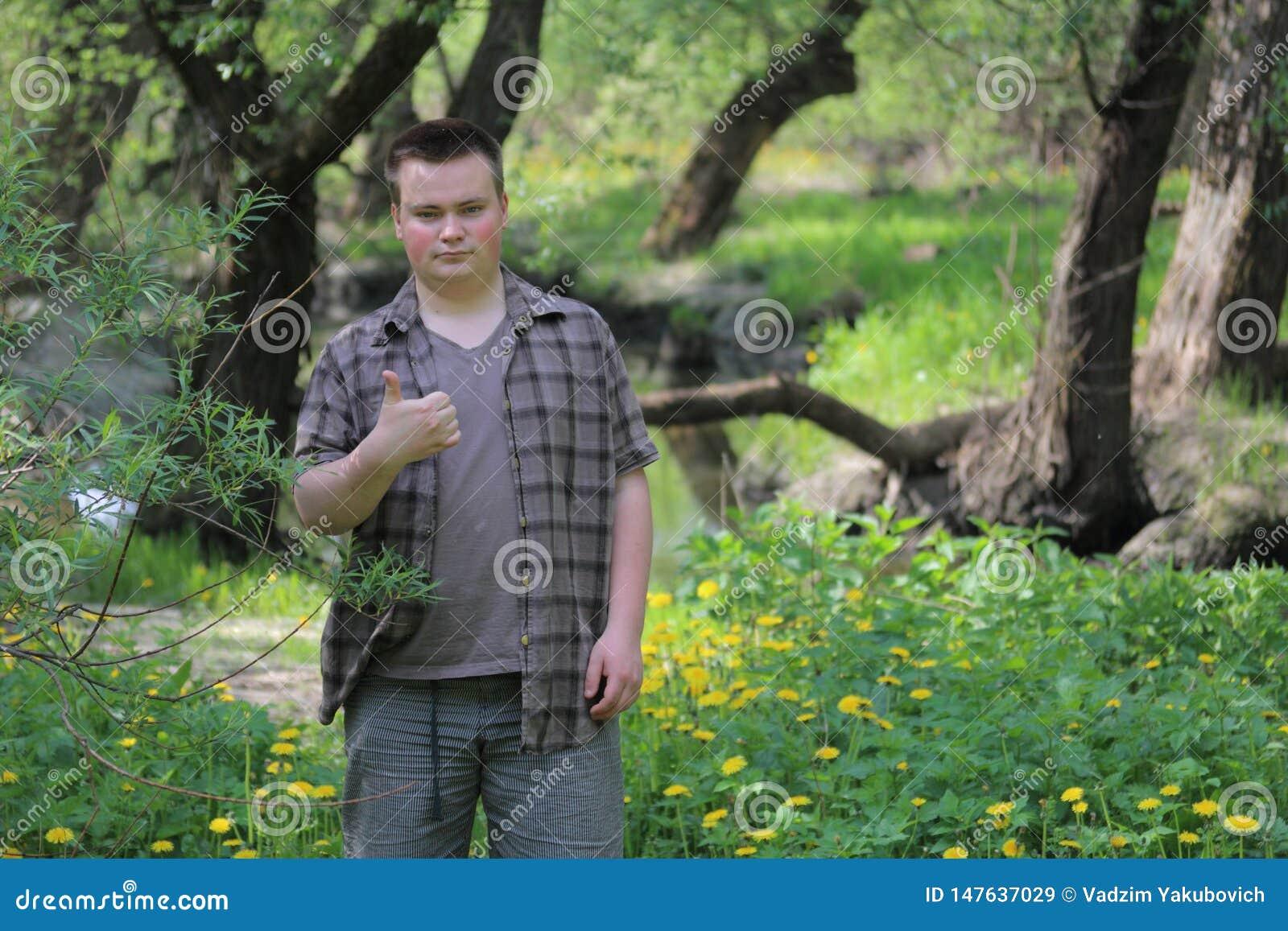 O homem gordo novo está com o o seu de volta ao rio Aumentou acima o polegar As mostras gostam No parque entre a folha verde-clar