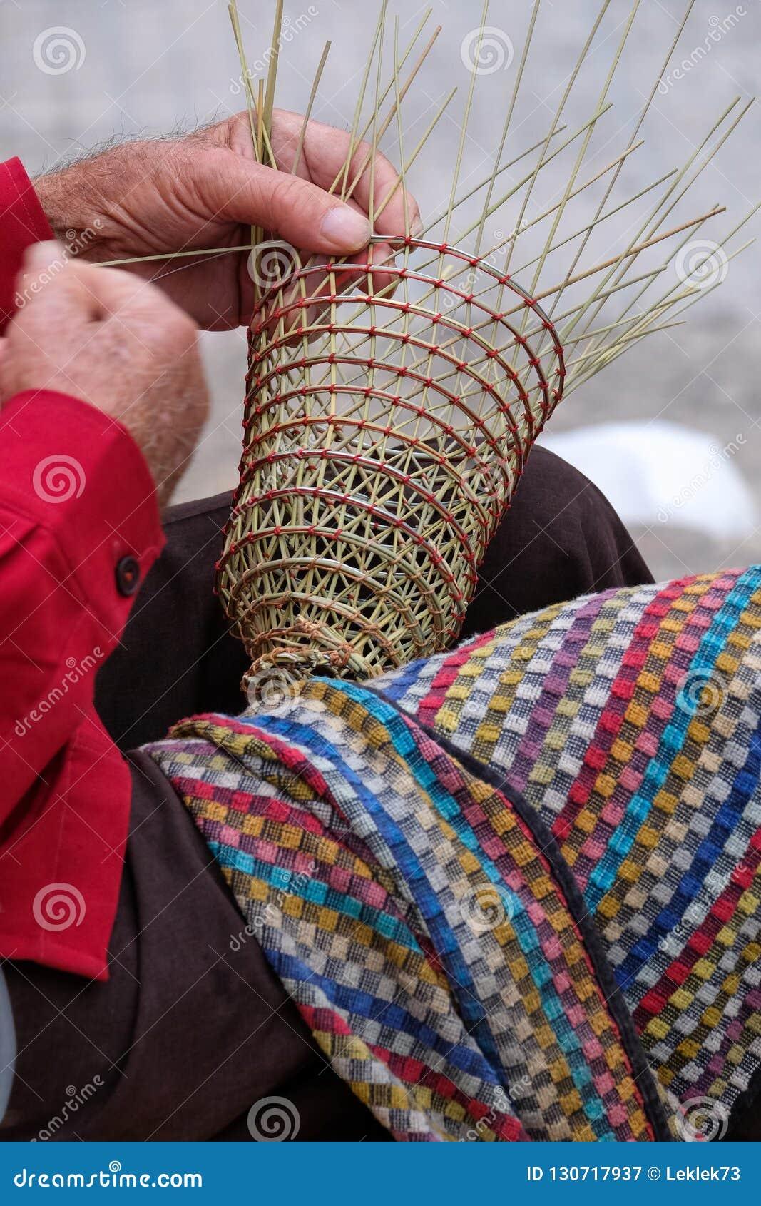 O homem idoso faz cestas para o uso na indústria de pesca na maneira tradicional, em Gallipoli, Puglia, Itália
