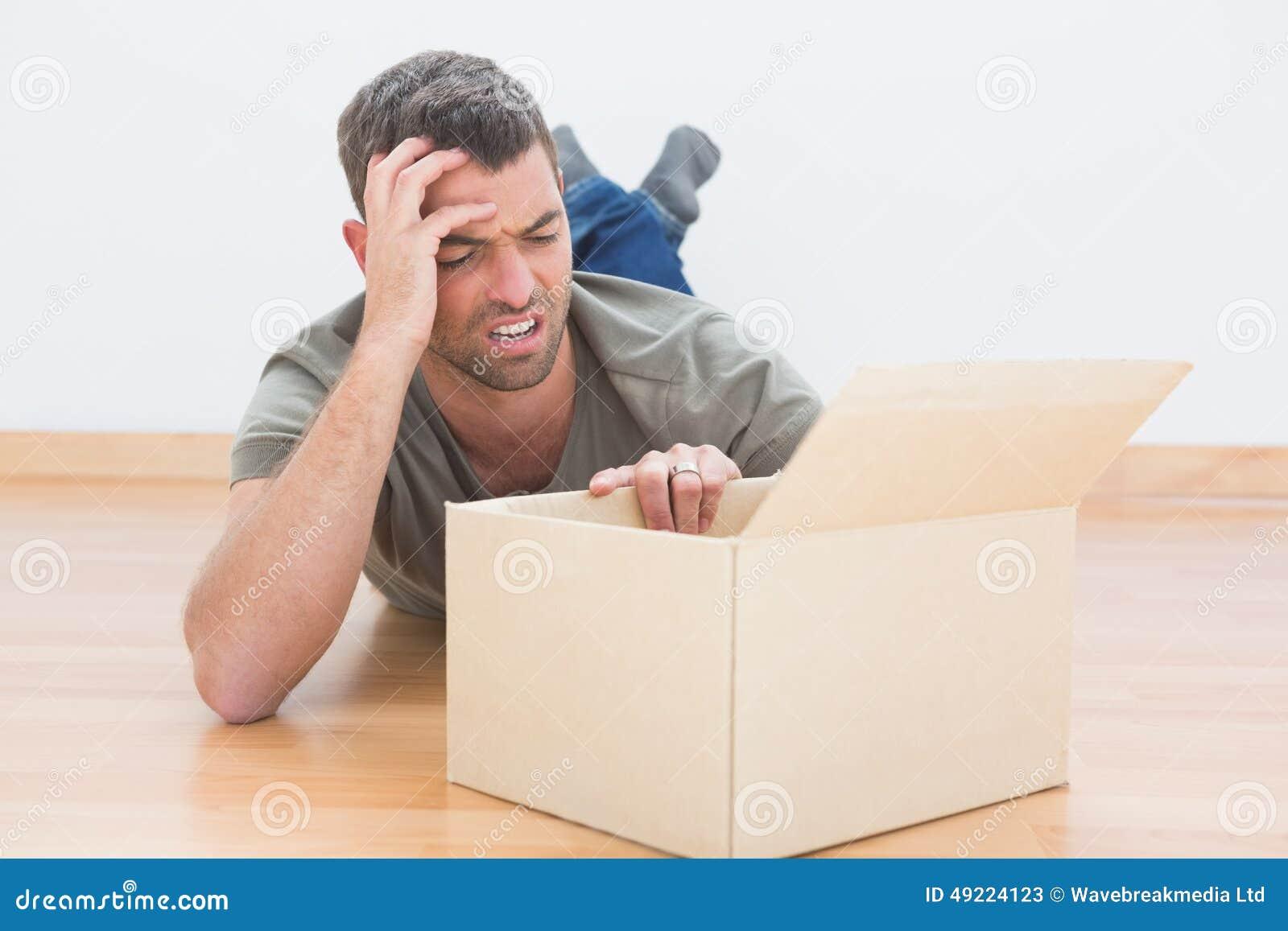 O homem incomodado abre uma caixa movente em casa