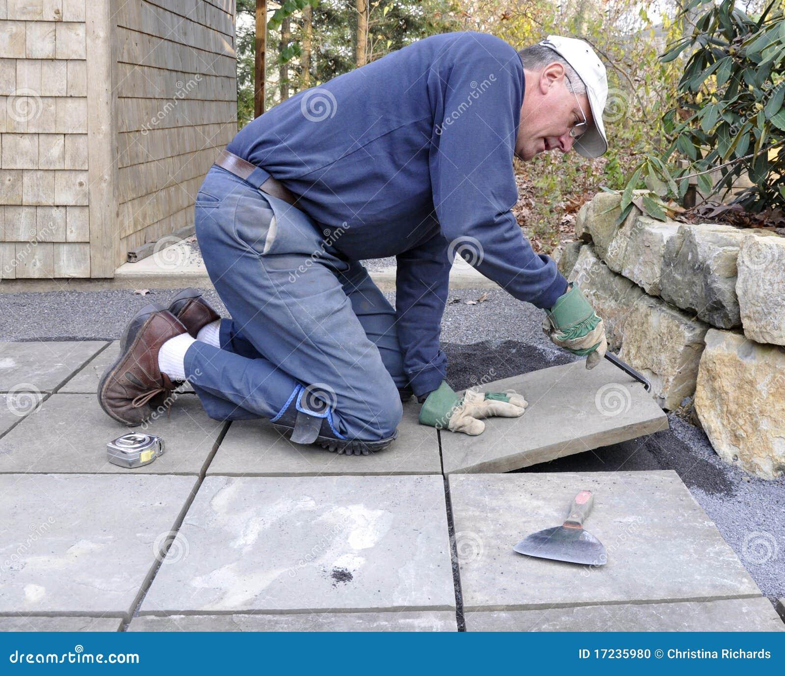 O homem instala o flagstone no pátio