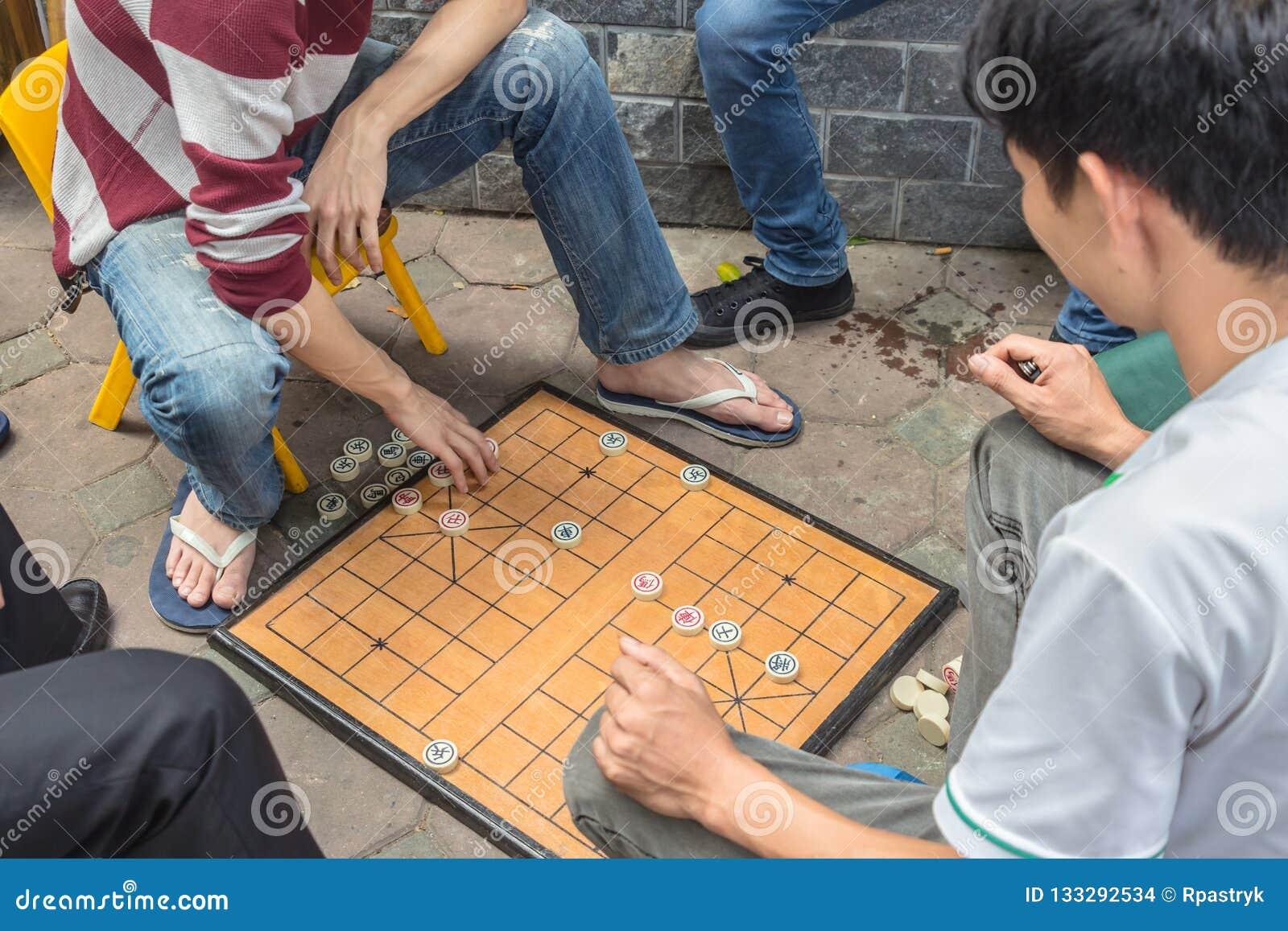 O homem irreconhecível joga o jogo de mesa tradicional conhecido como a xadrez chinesa