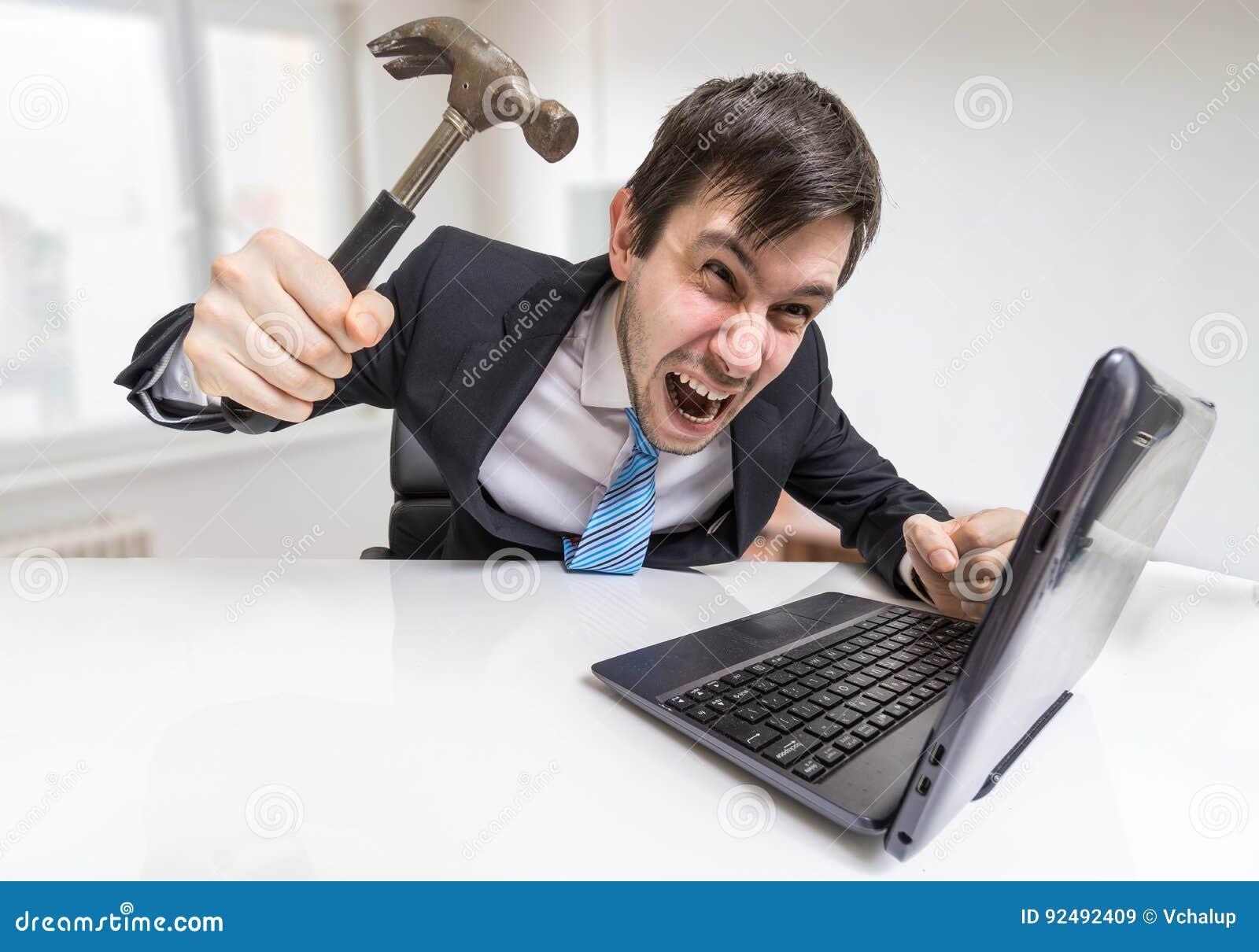 O homem irritado e louco está trabalhando com portátil Está indo danificar o caderno com martelo