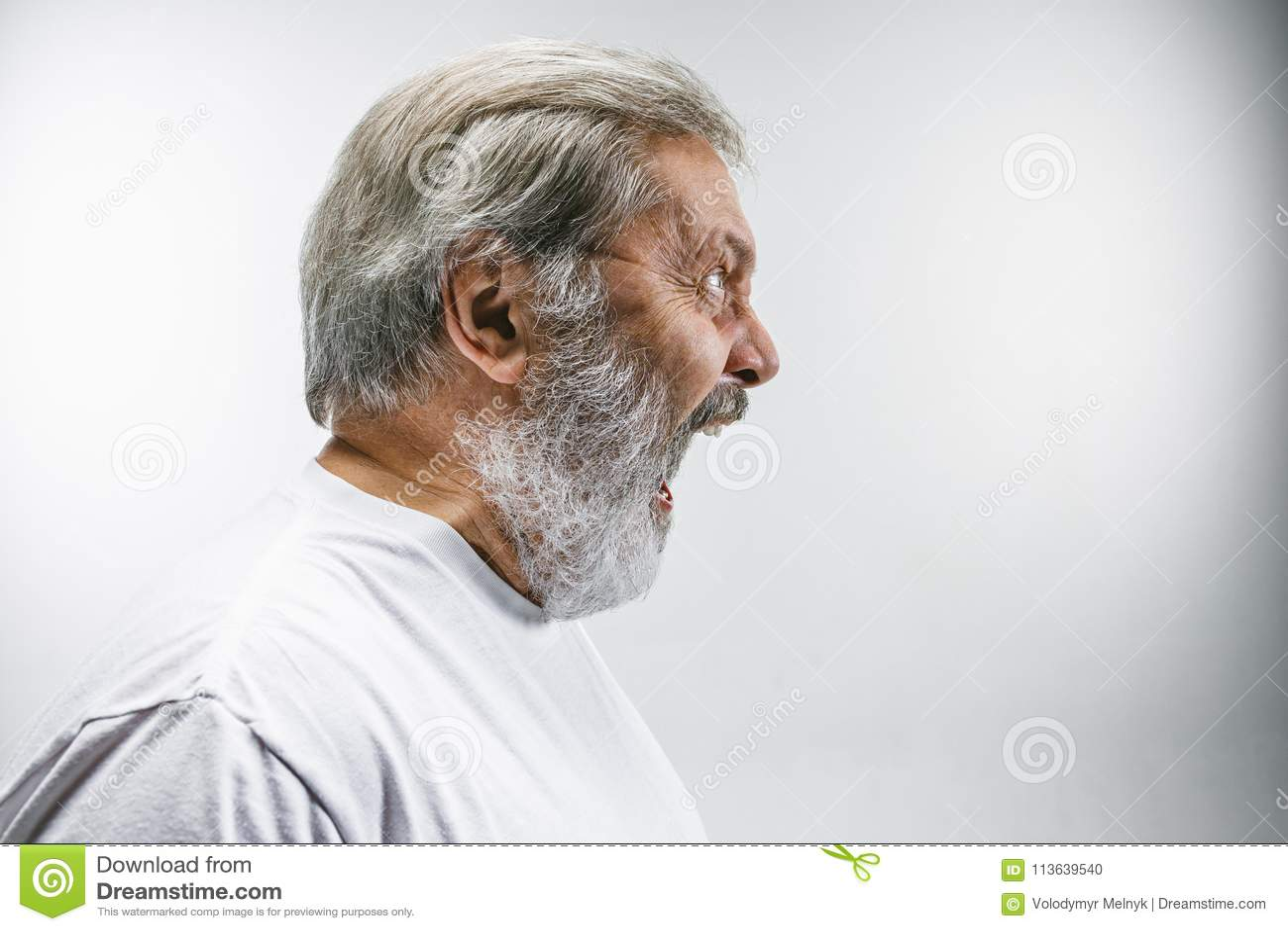 O homem irritado emocional superior que grita no fundo branco do estúdio