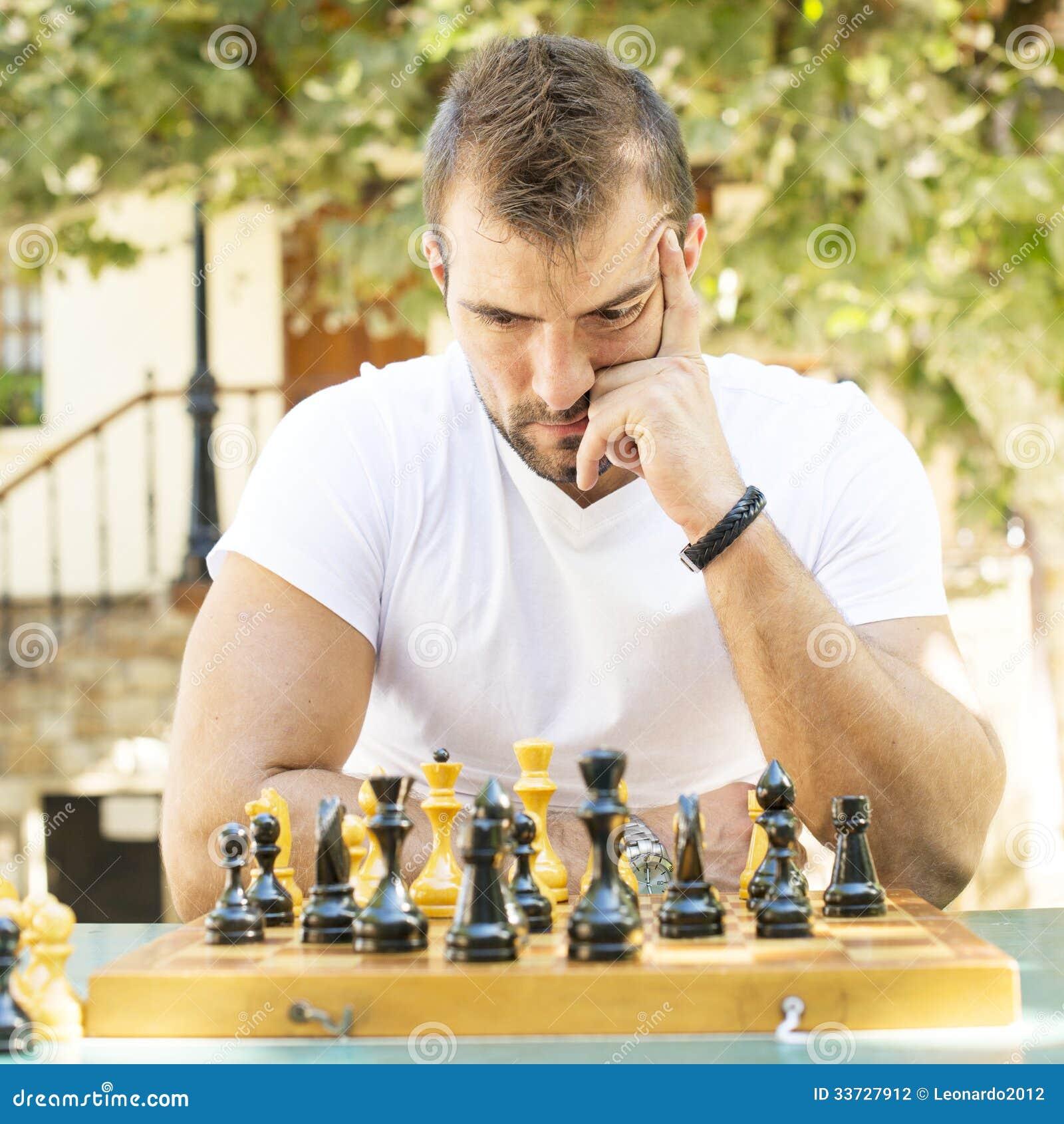 O homem joga a xadrez.