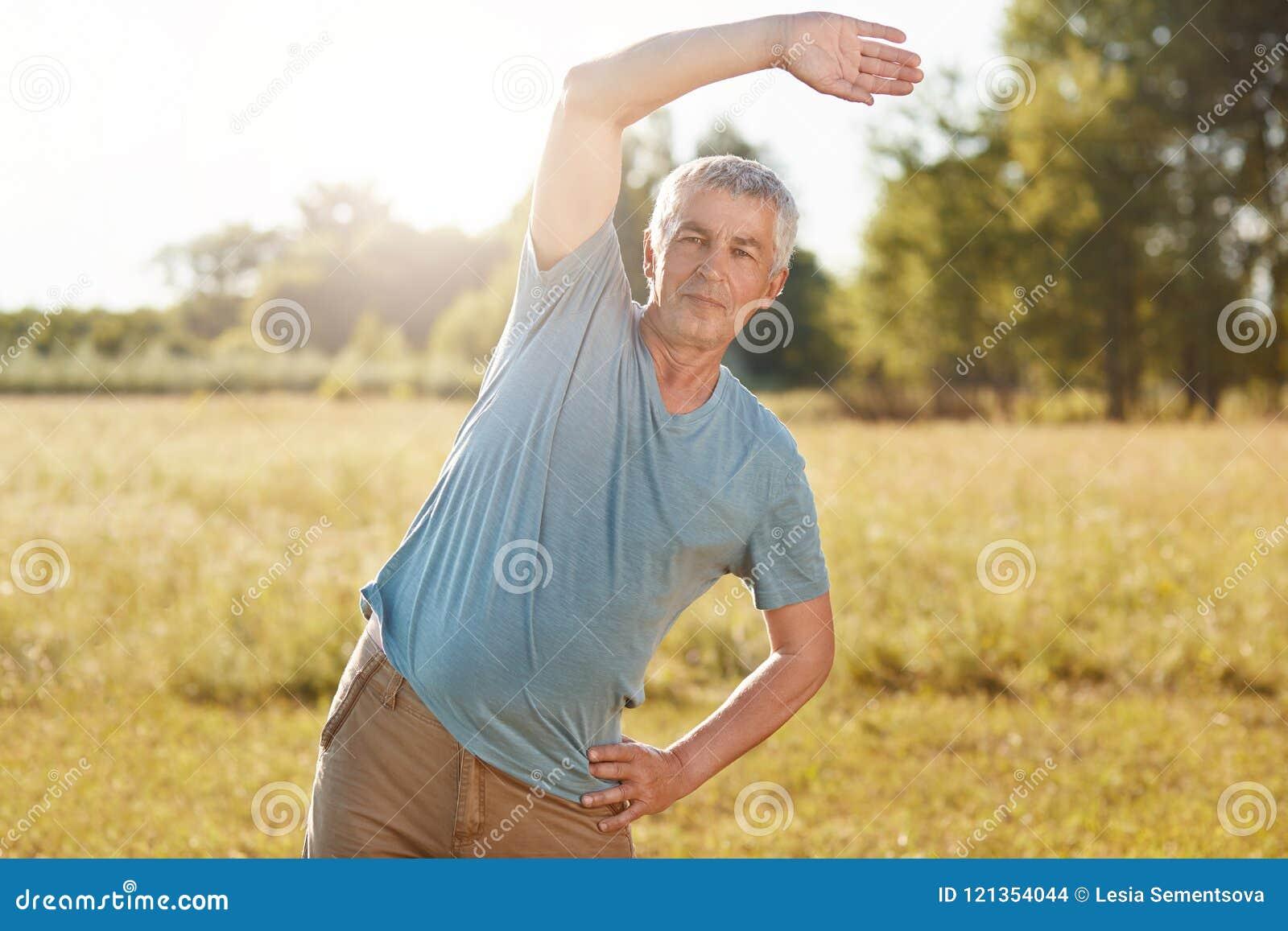 O homem maduro atlético com corpo do ajuste, curvaturas de lado, faz o exercício físico exterior, poses contra o fundo verde do c