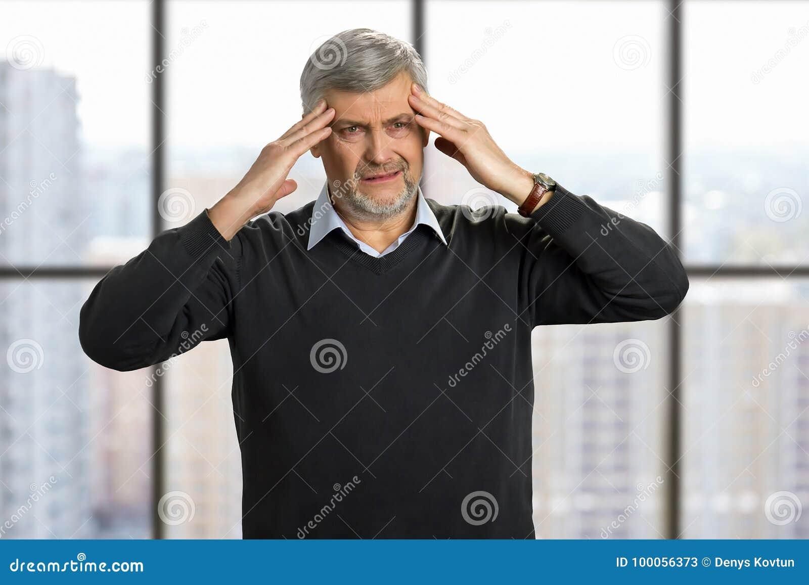 O homem maduro tem a dor de cabeça forte