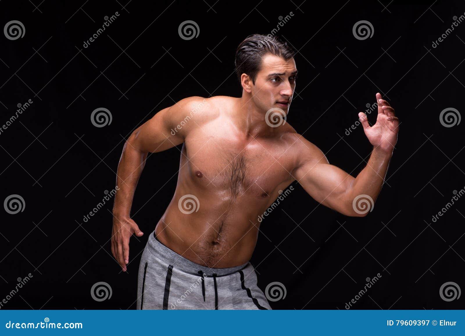 O homem muscular rasgado no fundo preto