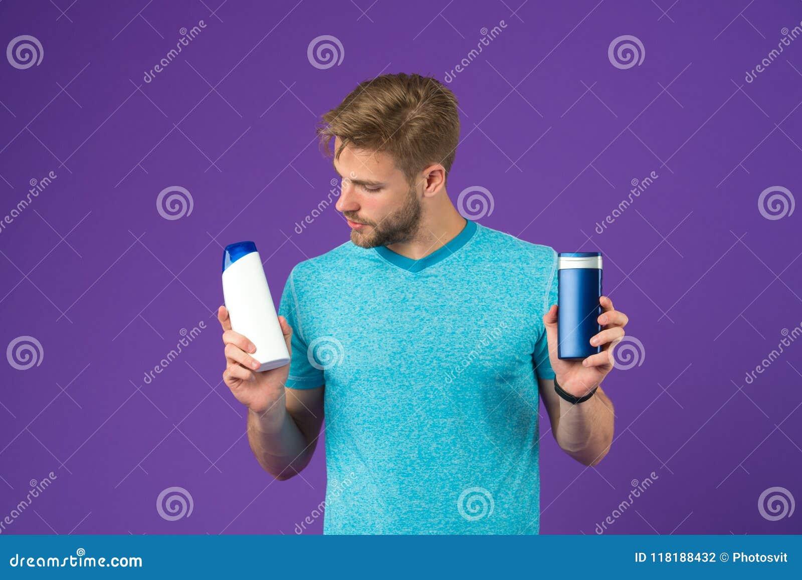 O homem na cara pensativa escolhe o champô, fundo violeta O indivíduo com cerda guarda duas garrafas com champô, espaço da cópia