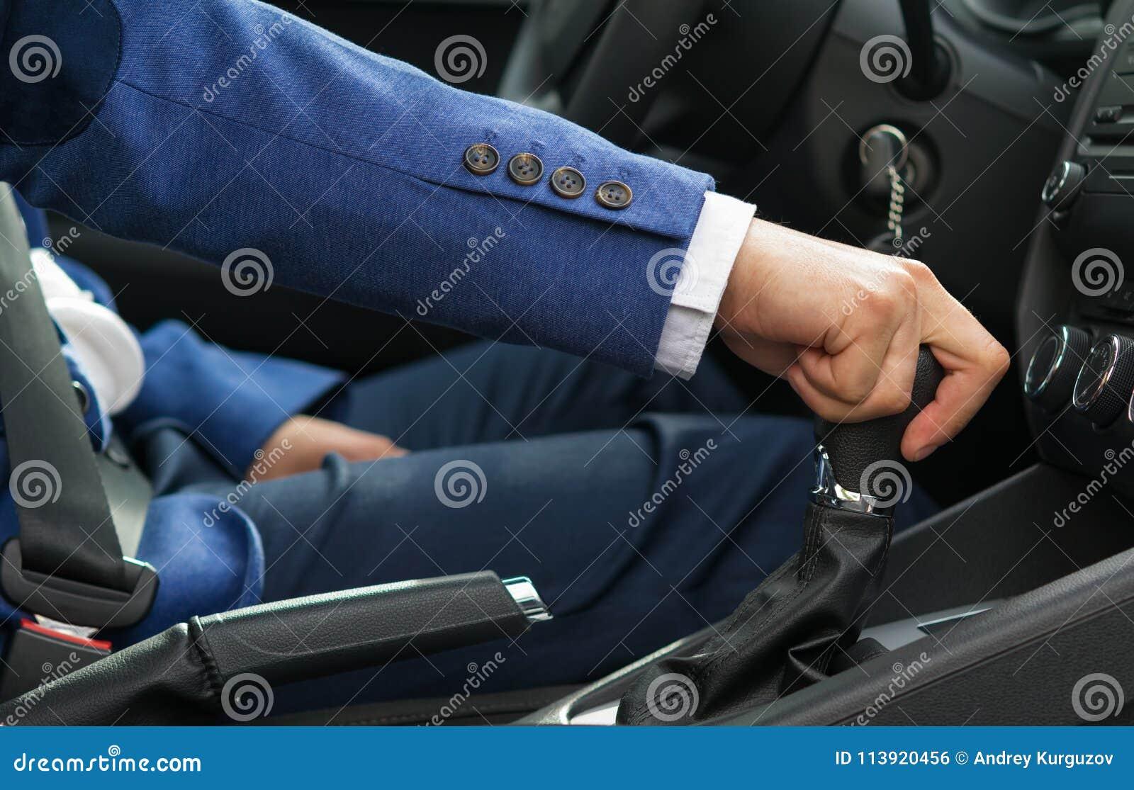 O homem no carro está guardando o botão do deslocamento da velocidade do ` s do carro