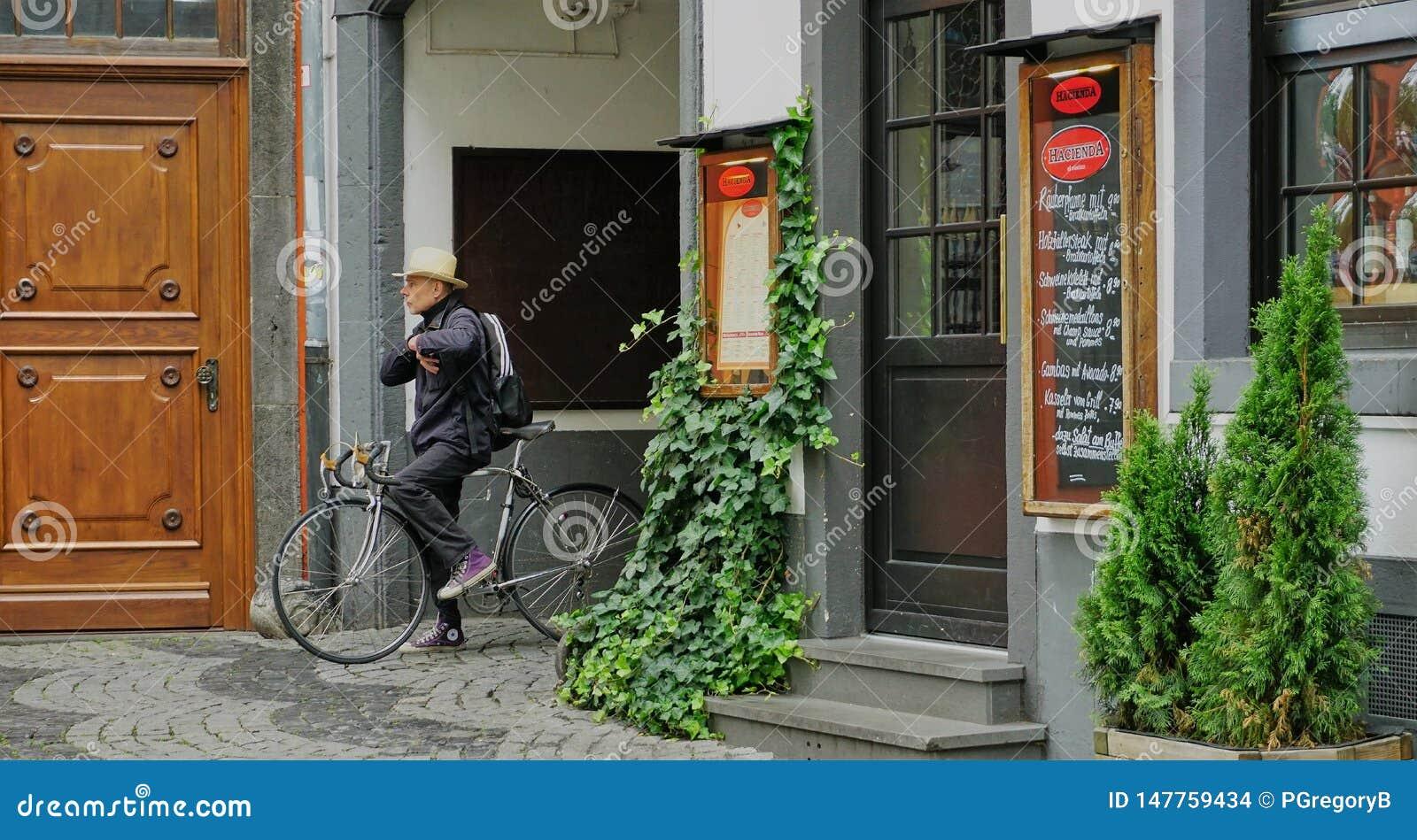 O homem no chapéu toma uma ruptura ao sentar-se na bicicleta na água de Colônia velha da cidade