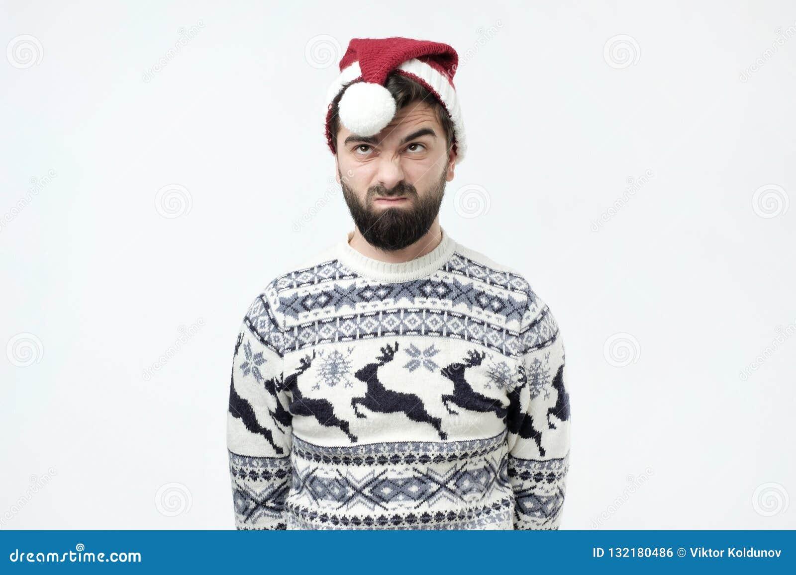 O homem no chapéu vermelho do Natal olha de sobrancelhas franzidas cara com descontentamento, irritou a expressão, sendo desconte