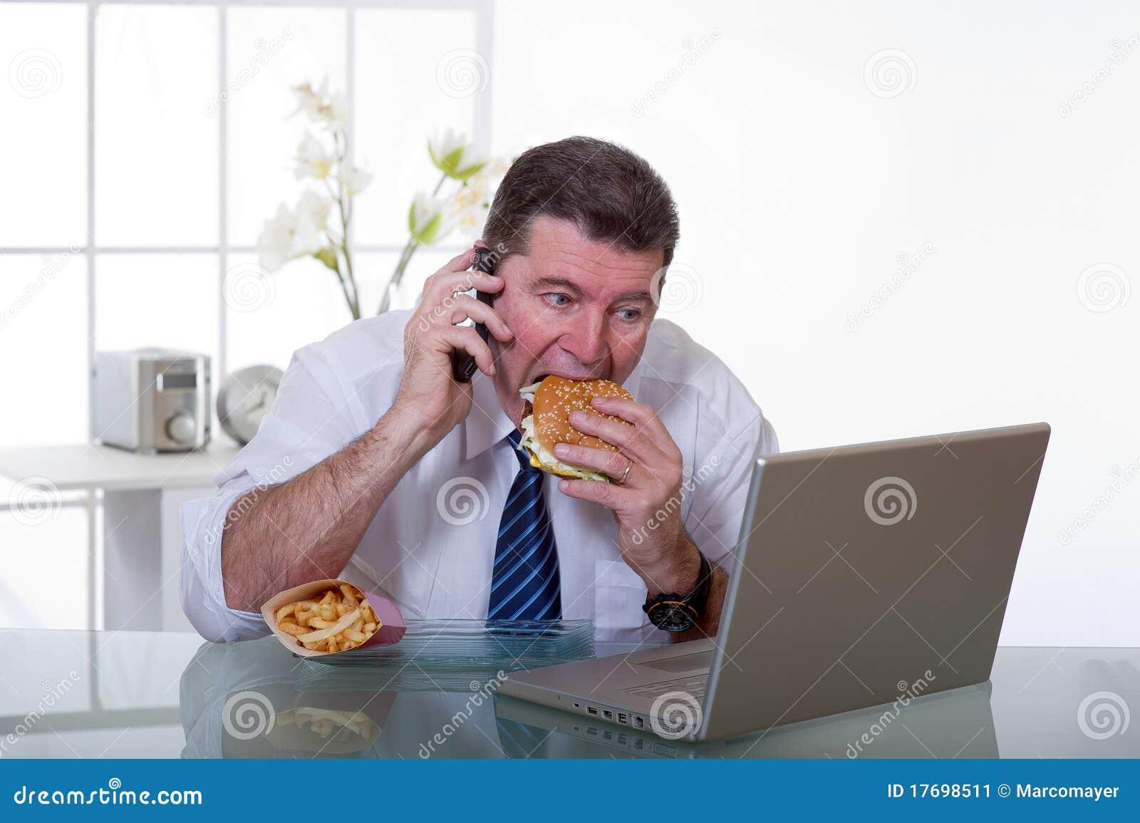 O homem no escritório come o alimento insalubre