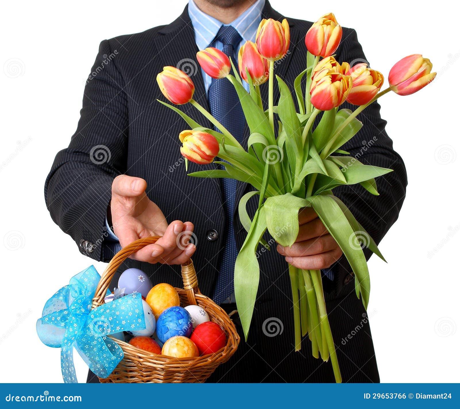 O homem no terno e no laço dá tulipas e cesta de Easter