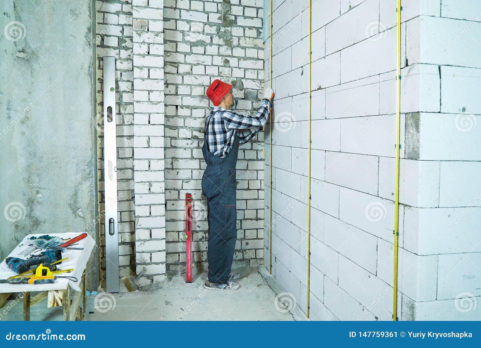 O homem no trabalho veste a instalação dos trilhos do metal na parede ventilada do bloco de cimento