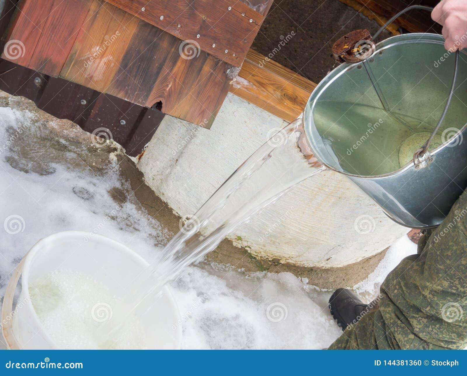 O homem no uniforme militar pegara a água de um poço no inverno