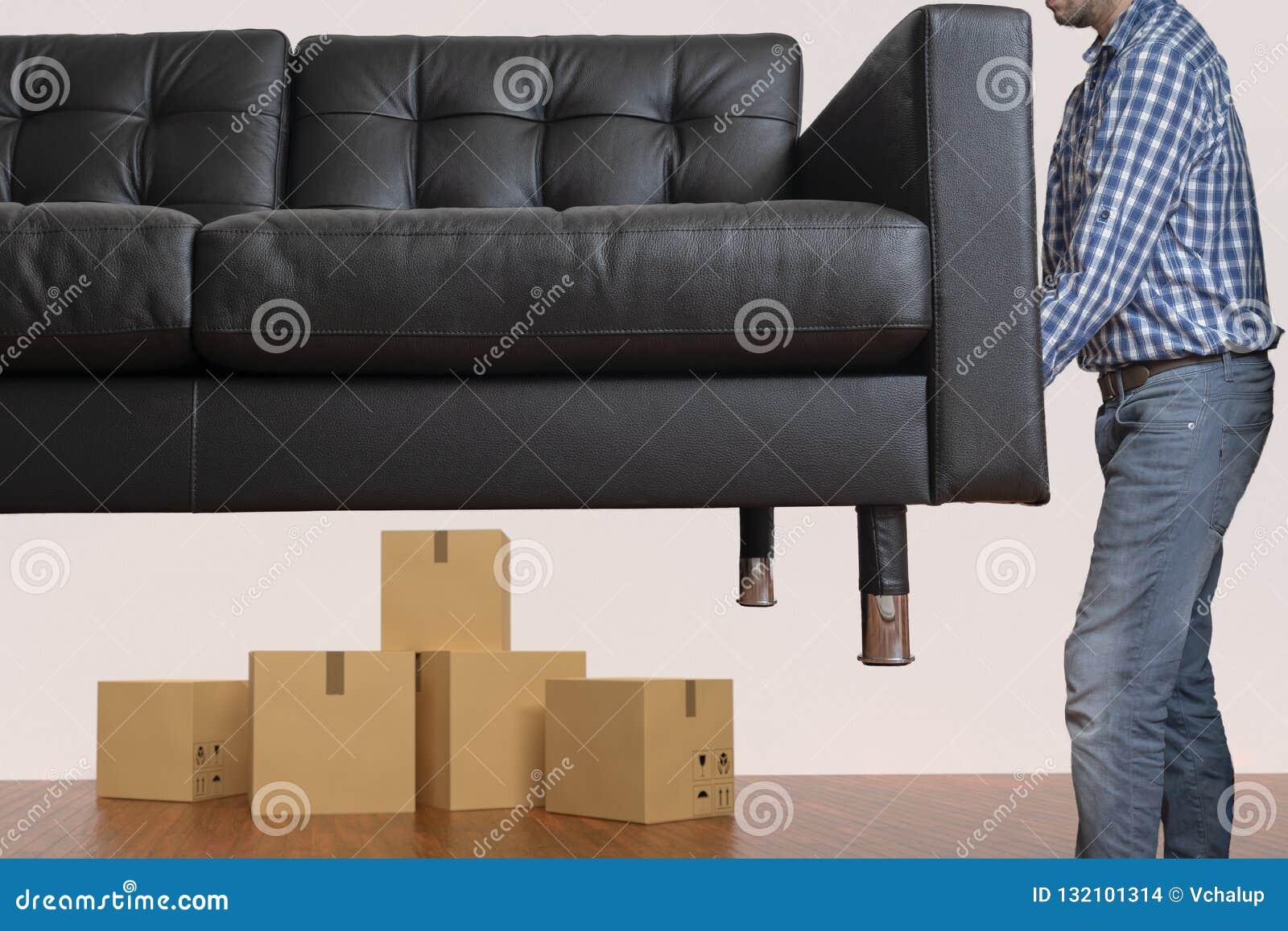 O homem novo é sofá movente Mover-se para um conceito da casa nova