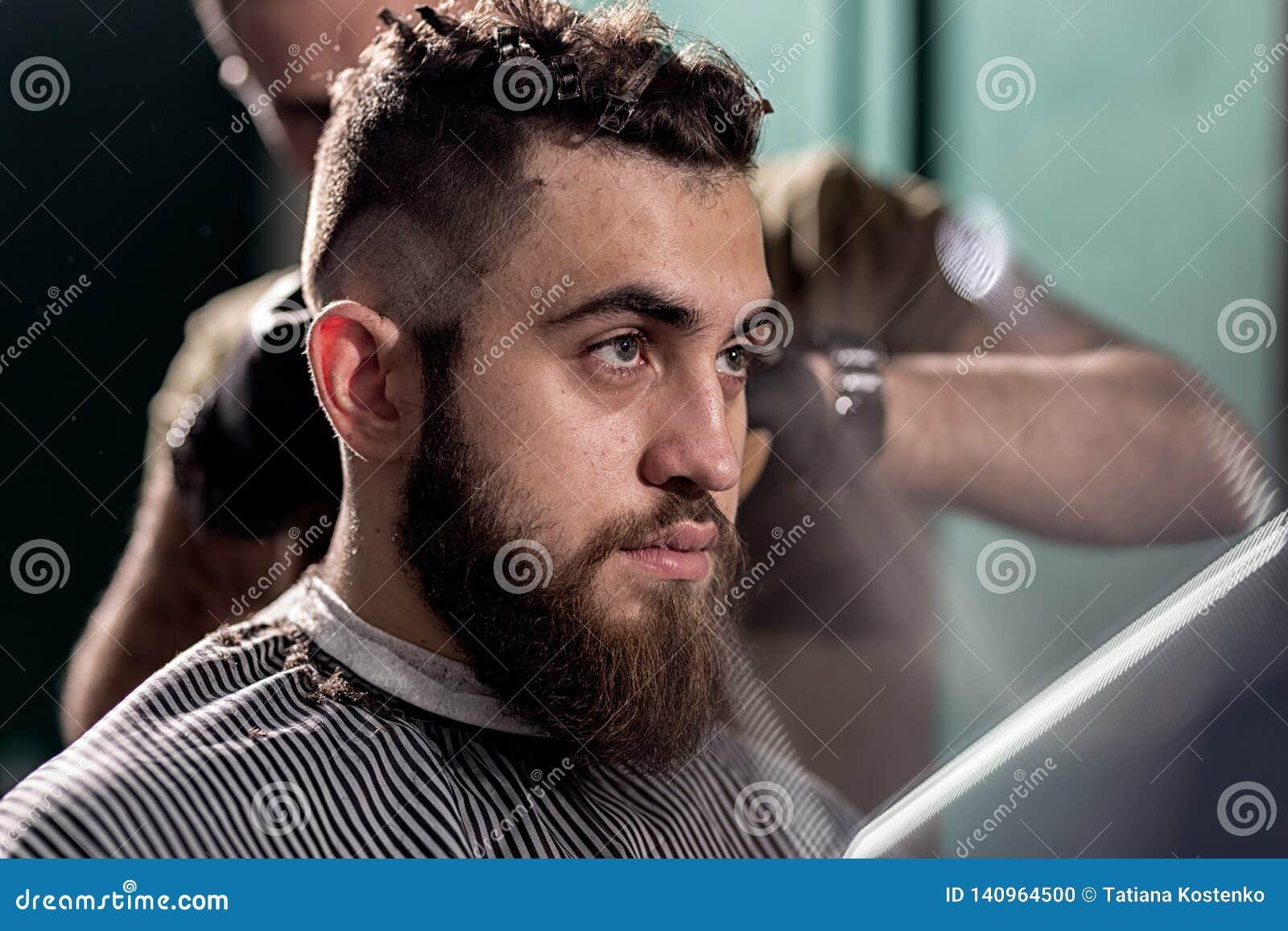 O homem novo considerável com barba senta-se em uma barbearia O barbeiro barbeia os cabelos na parte traseira