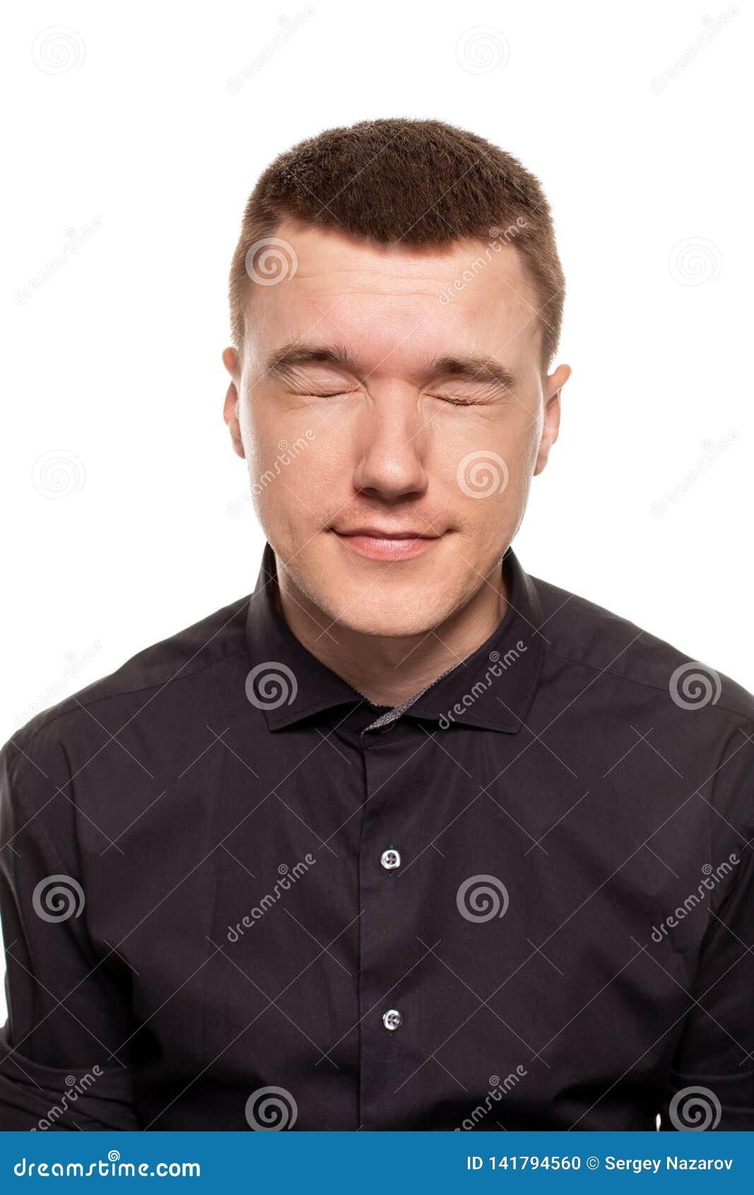 O homem novo considerável em uma camisa preta está fazendo as caras, ao estar isolado em um fundo branco