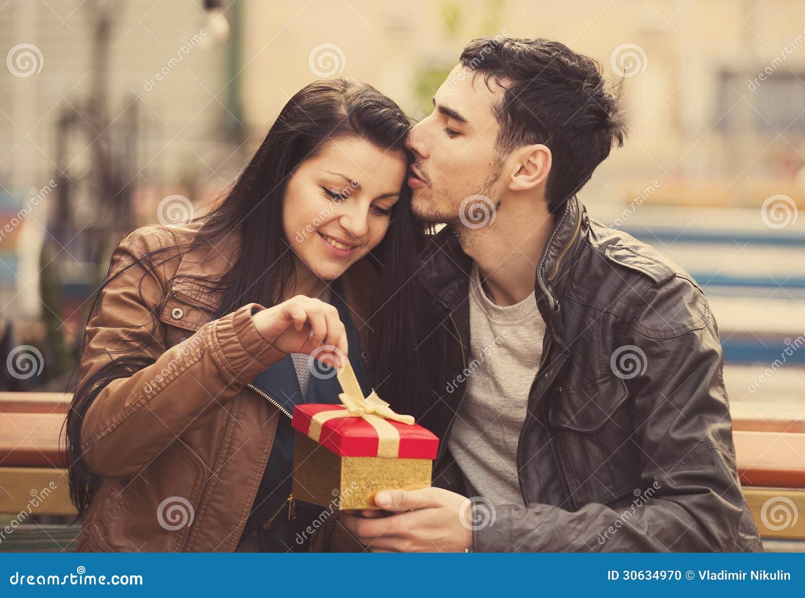 O homem novo dá um presente a uma rapariga no café e nos eles