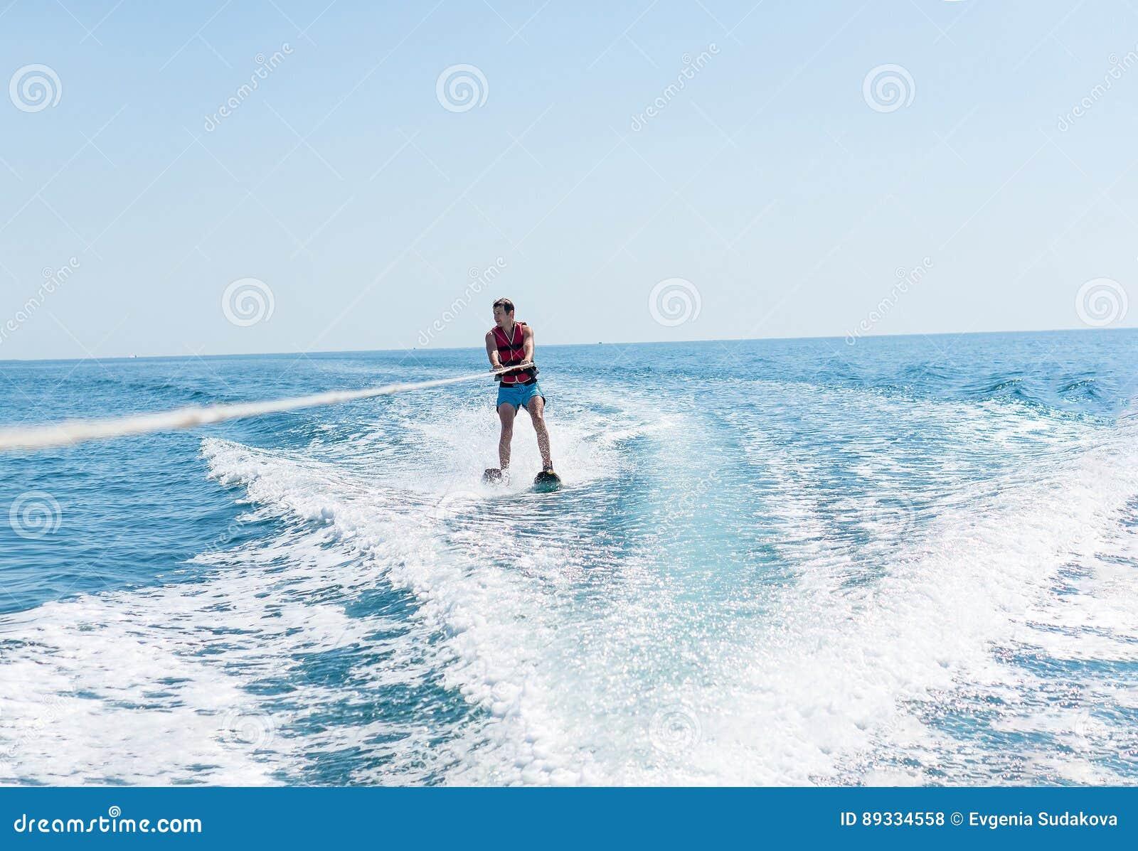O homem novo desliza no esqui aquático nas ondas no mar, oceano Estilo de vida saudável Emoções humanas positivas, sentimentos,