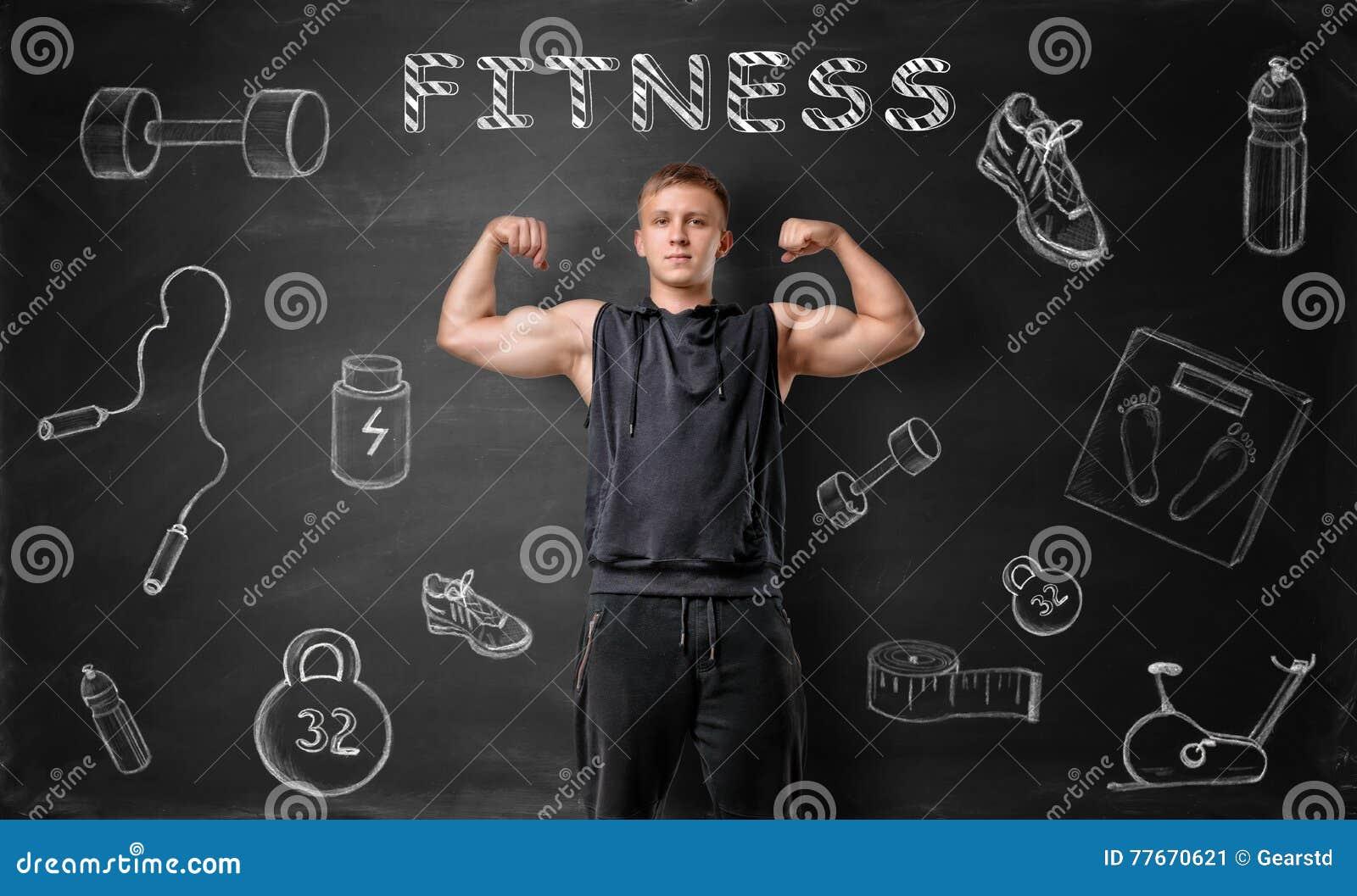 O homem novo Muscled que mostra seus músculos do bíceps no fundo do quadro-negro com aptidão rabisca