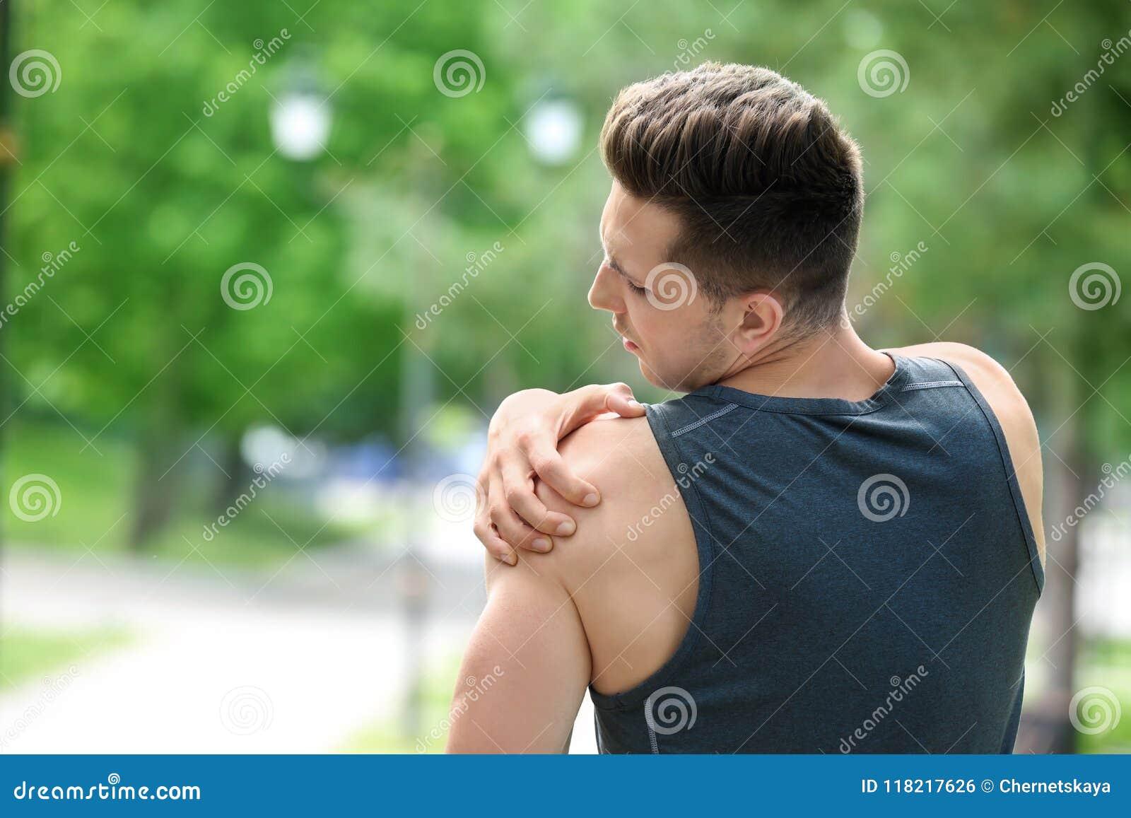O homem novo no sportswear que sofre do ombro causa dor fora
