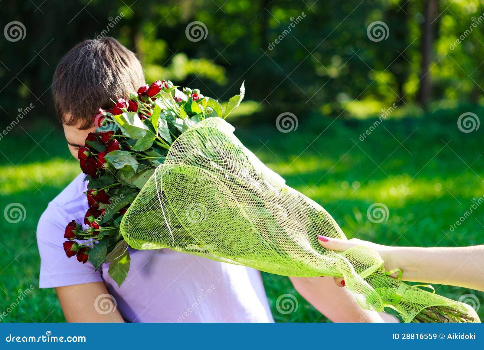 O homem novo obtem a batida no ramalhete da face de rosas vermelhas