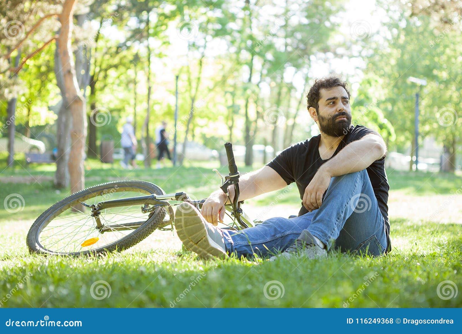 O homem novo olha ausente ao descansar na grama