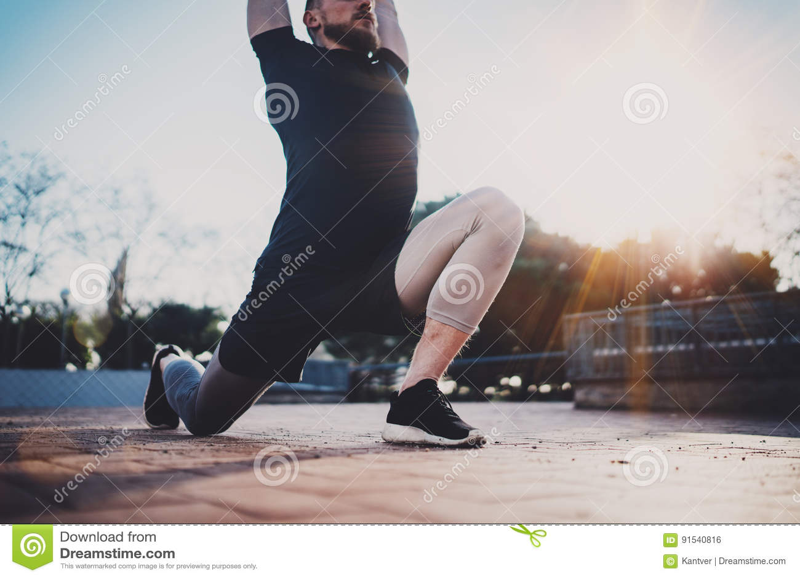 O homem novo que faz o estiramento exercita os músculos antes de treinar Conceito do estilo de vida do exercício Atleta muscular