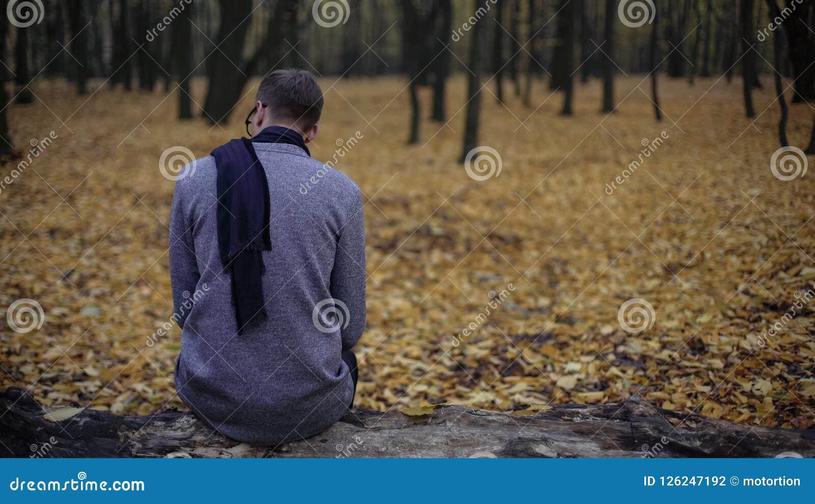 O homem novo que senta-se apenas no parque do outono, sente a depressão, nostalgia, solidão