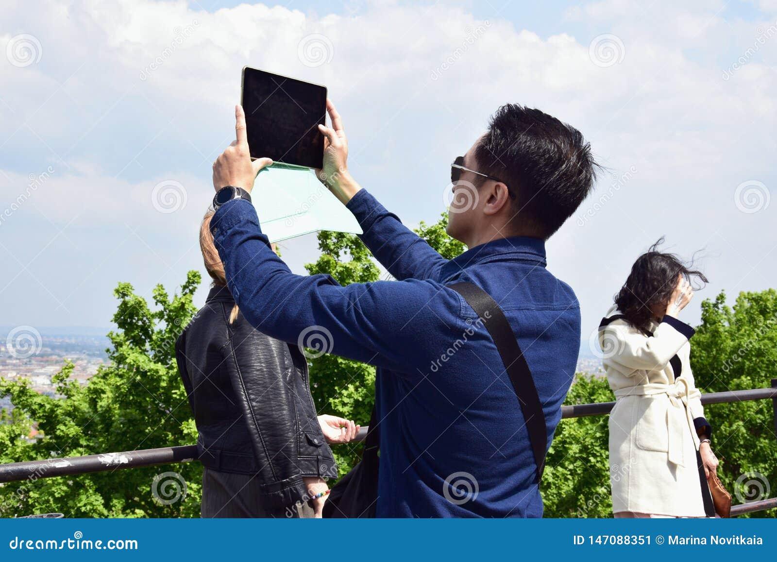 O homem novo toma uma imagem com uma tabuleta de uma vista pitoresca da cidade