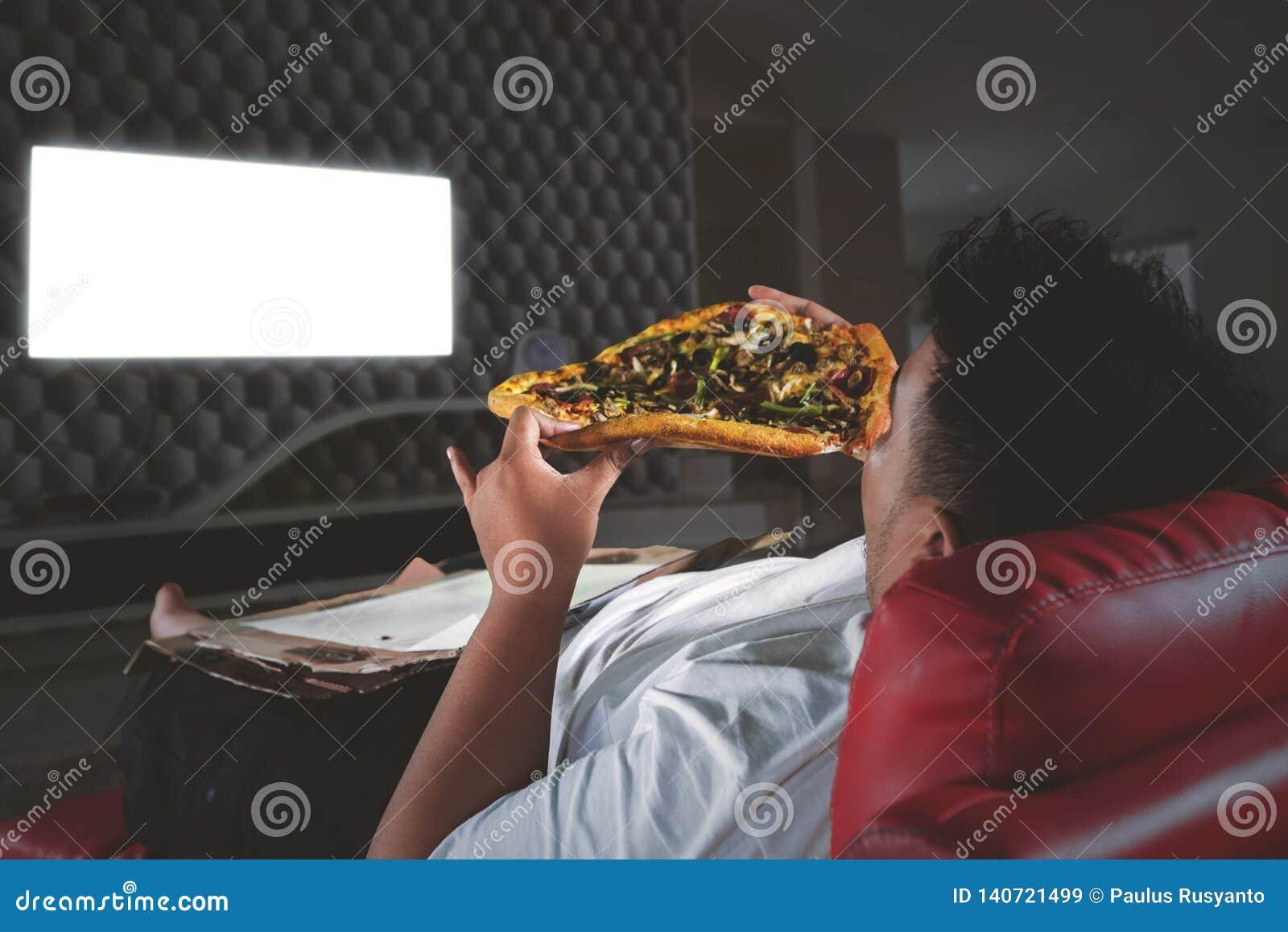 O homem obeso come a pizza na frente de uma tevê na noite