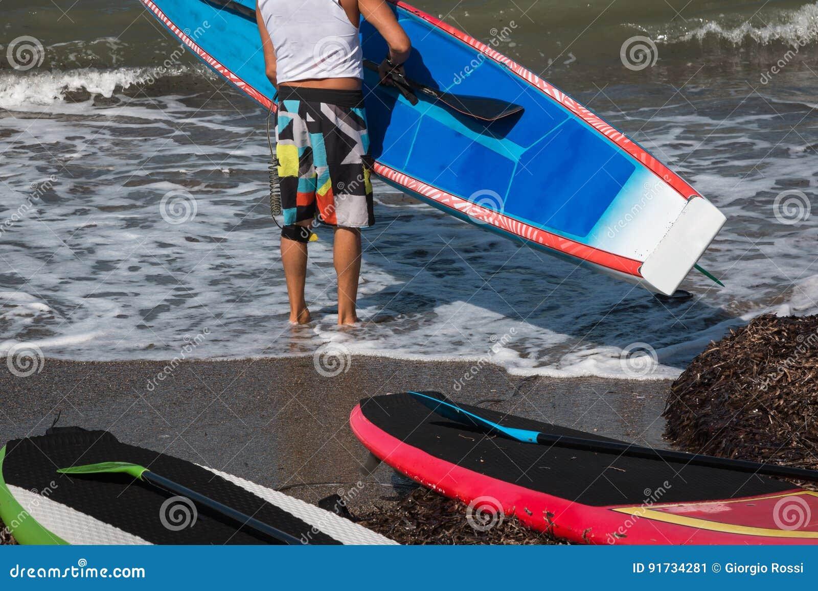 O homem pôs a placa na água na linha costeira