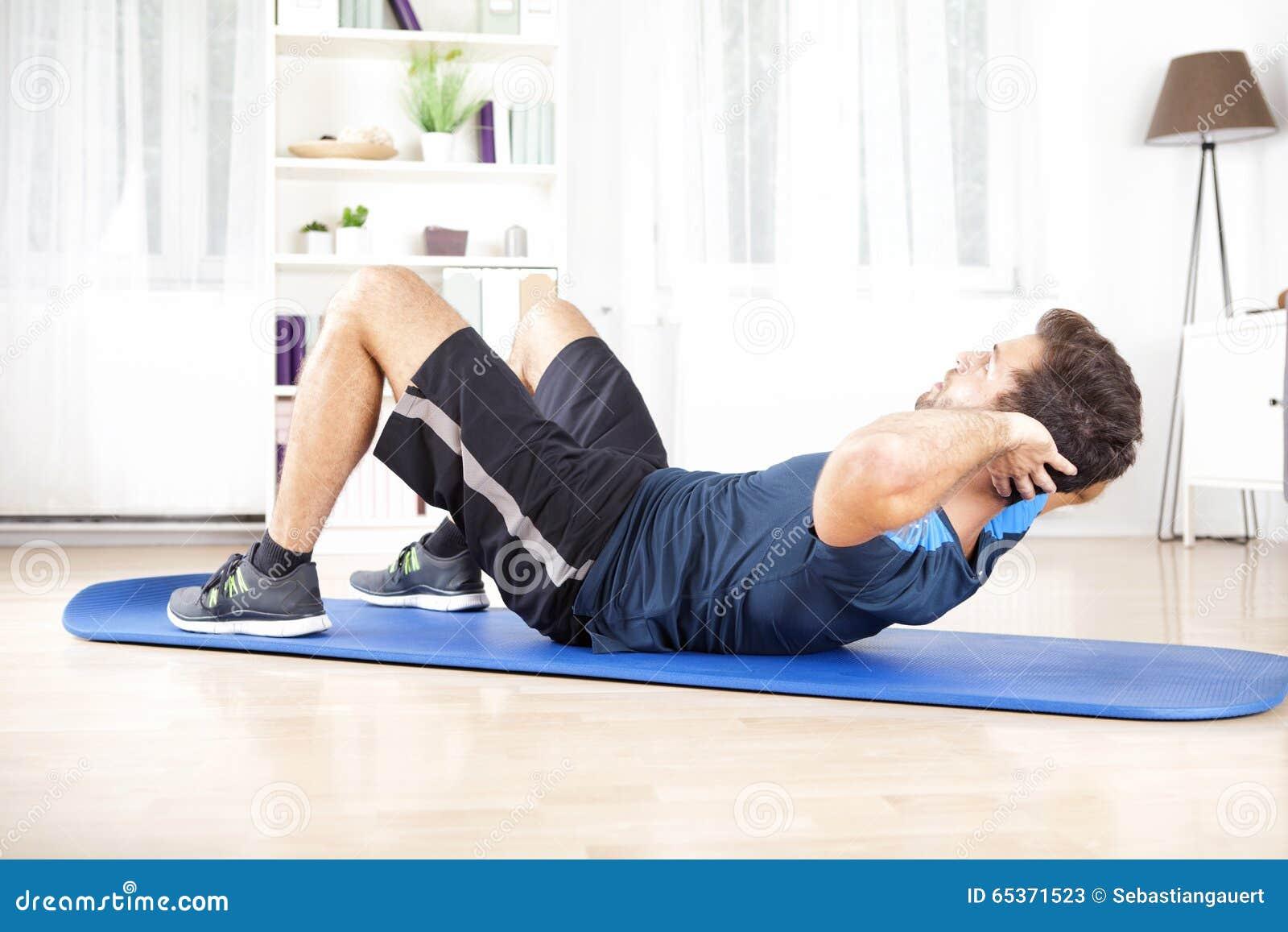 O homem que atlético fazer ondula levanta o exercício em casa