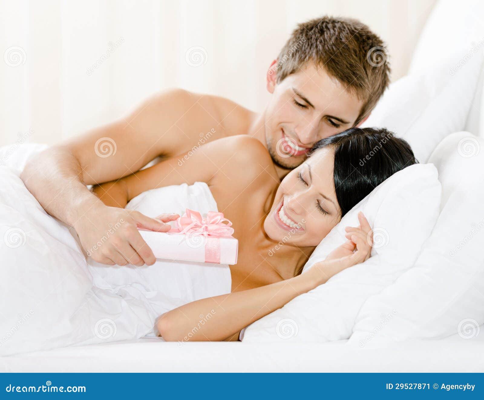 O homem que encontra-se no quarto dá o presente à mulher