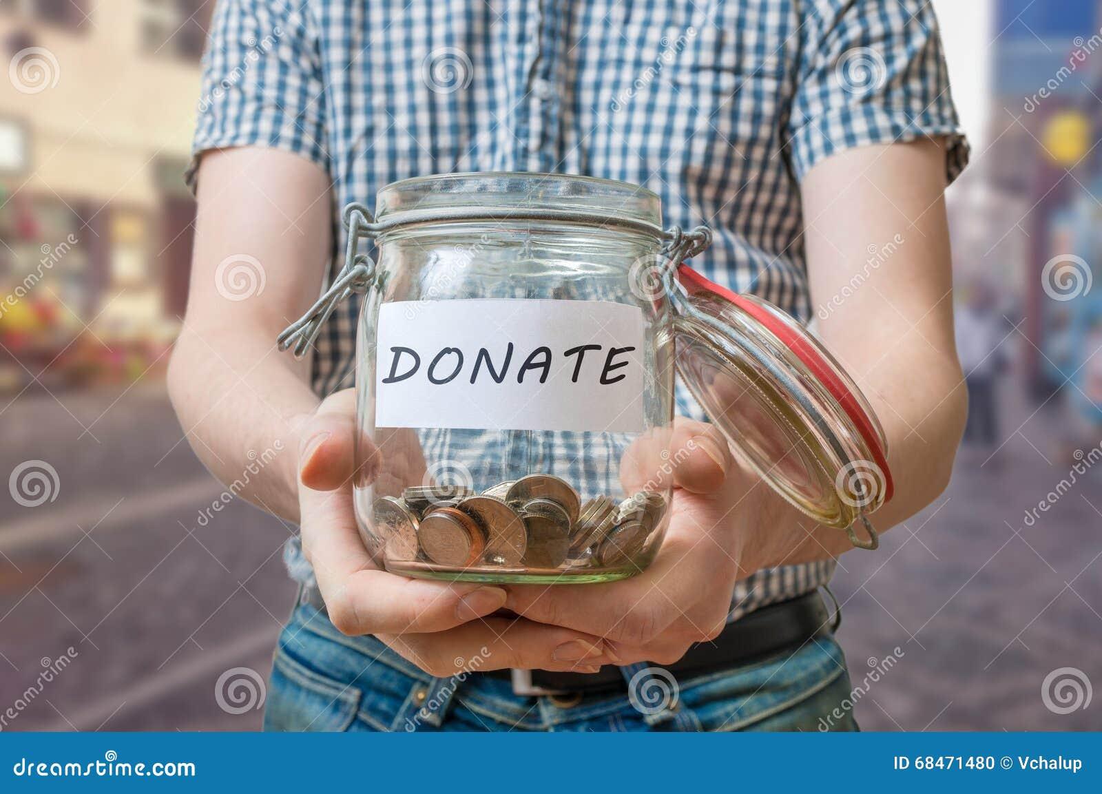 O homem que está na rua está recolhendo doações no frasco