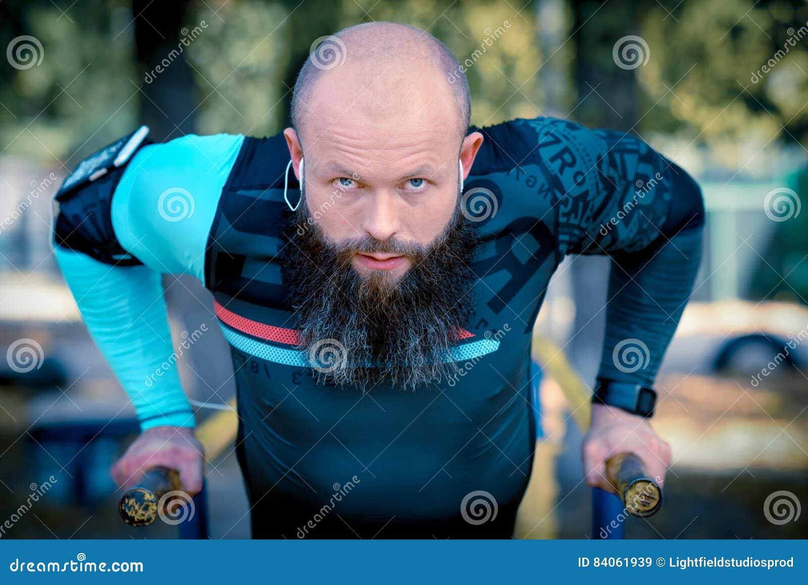 O homem que fazer empurra levanta em barras paralelas