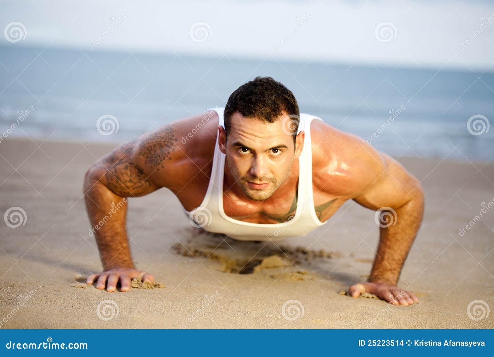 O homem que fazer empurra levanta em uma praia