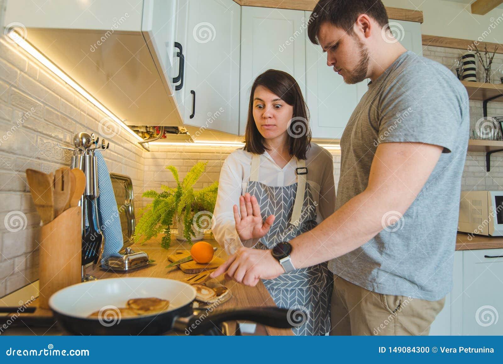 O homem roubar o alimento quando mulher que faz o café da manhã