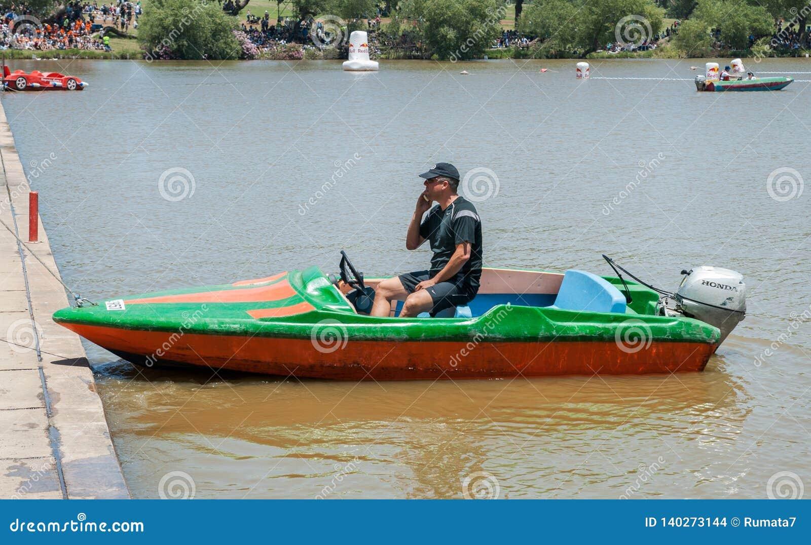 O homem senta-se no barco e na fala em seu telefone celular